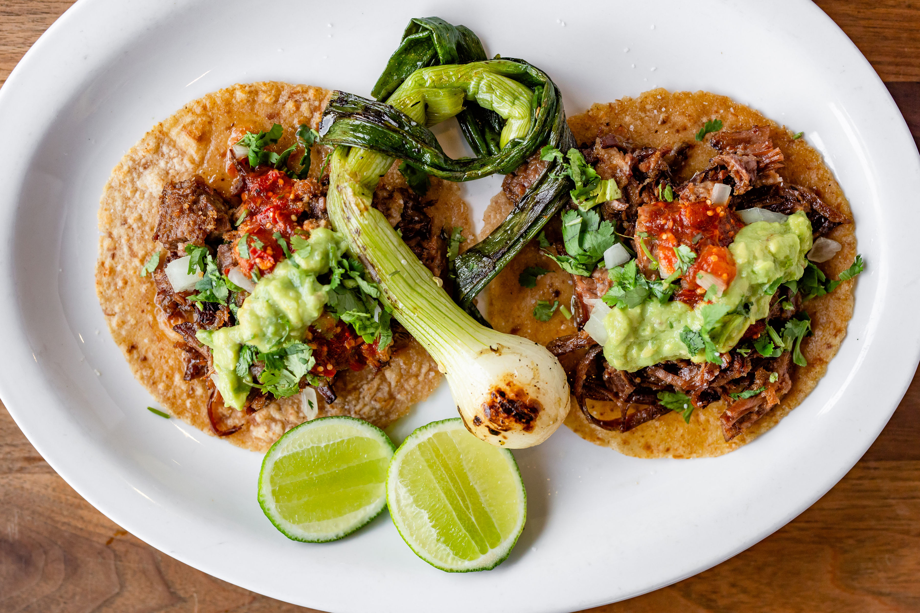 Two tacos and grilled spring onion
