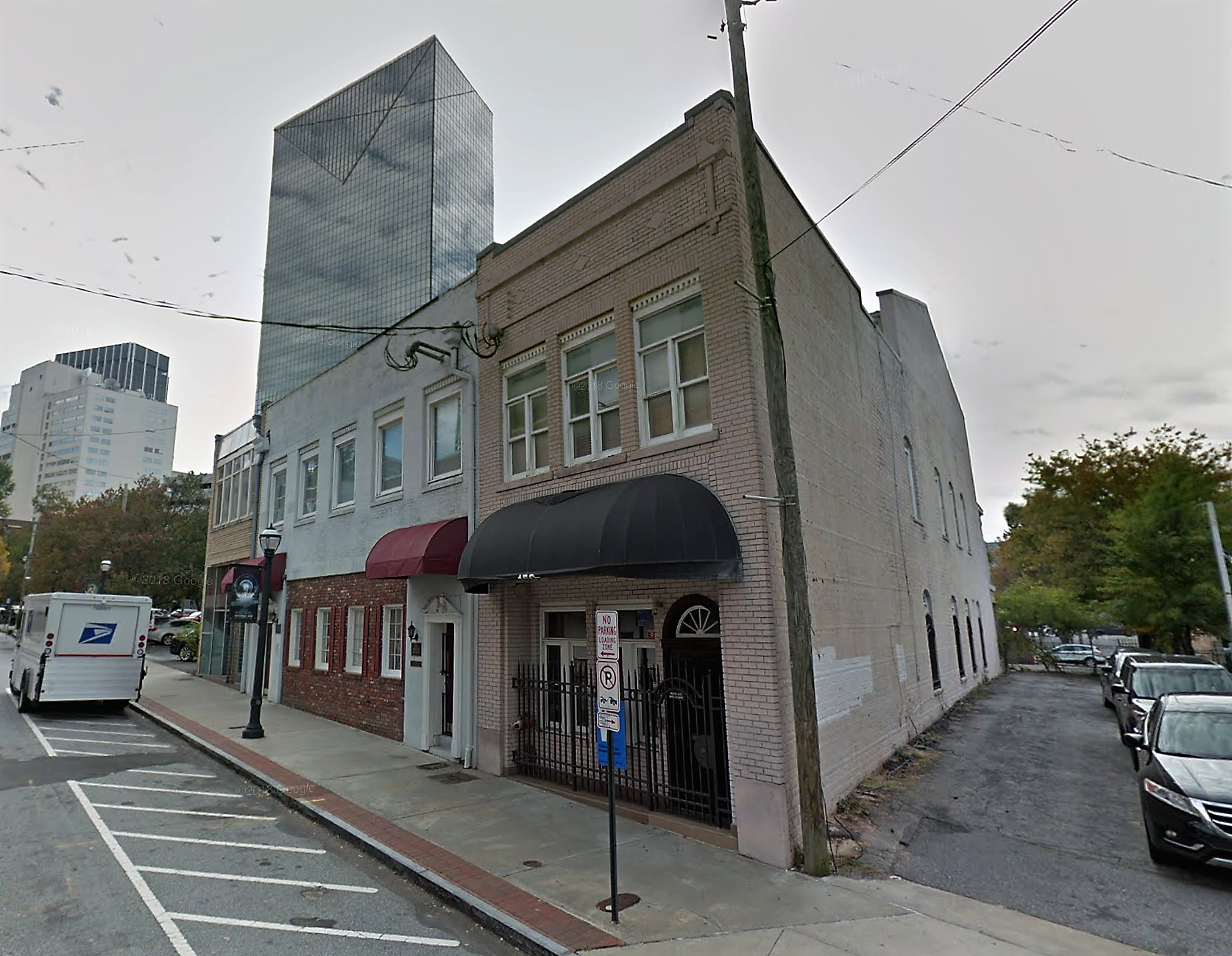 A picture of 152 Nassau Street, an aging grey brick building with a black awning, looking small in the shadow of a downtown skyscraper.