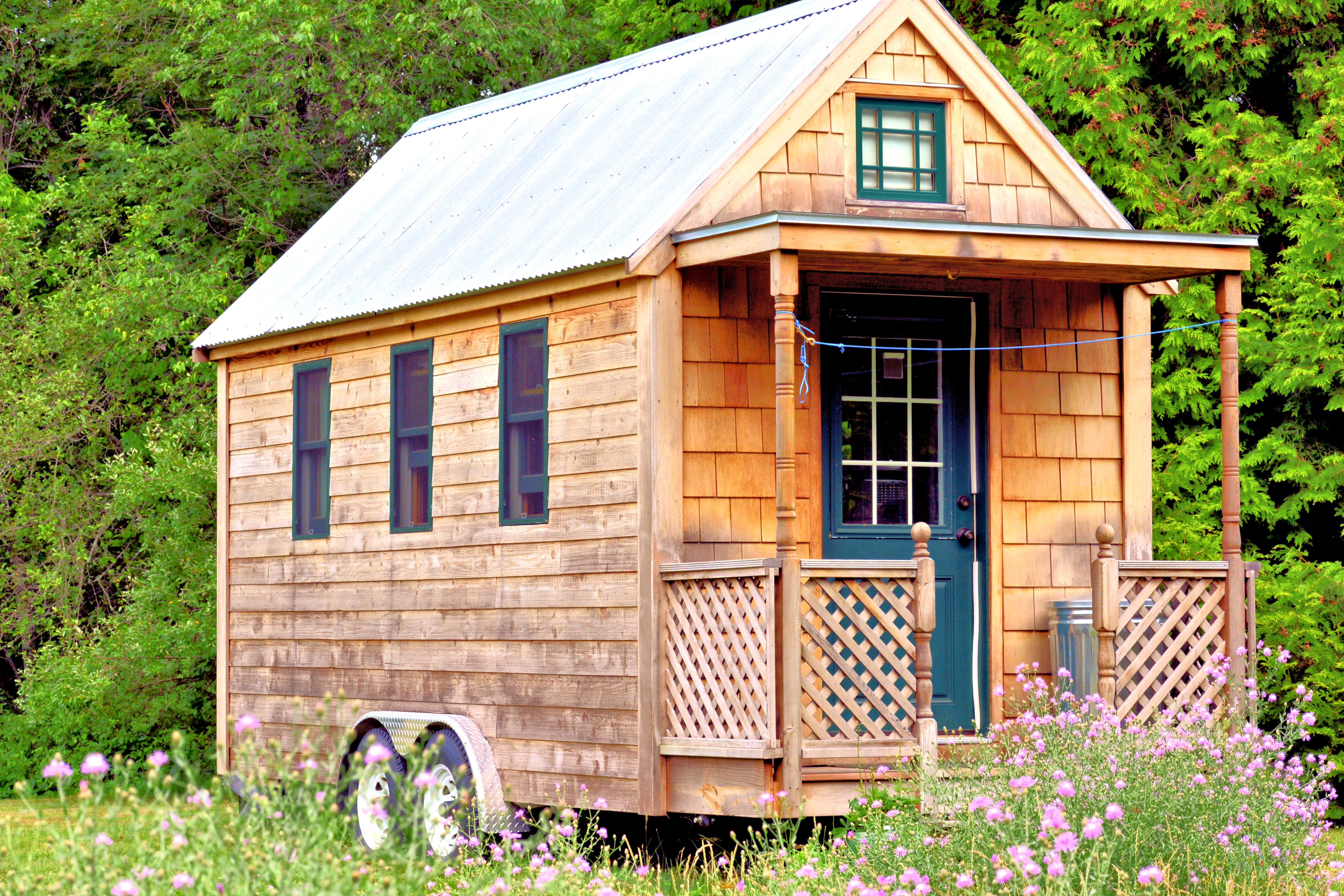 Wooden pitch-roofed tiny house with porch on a verdant site.