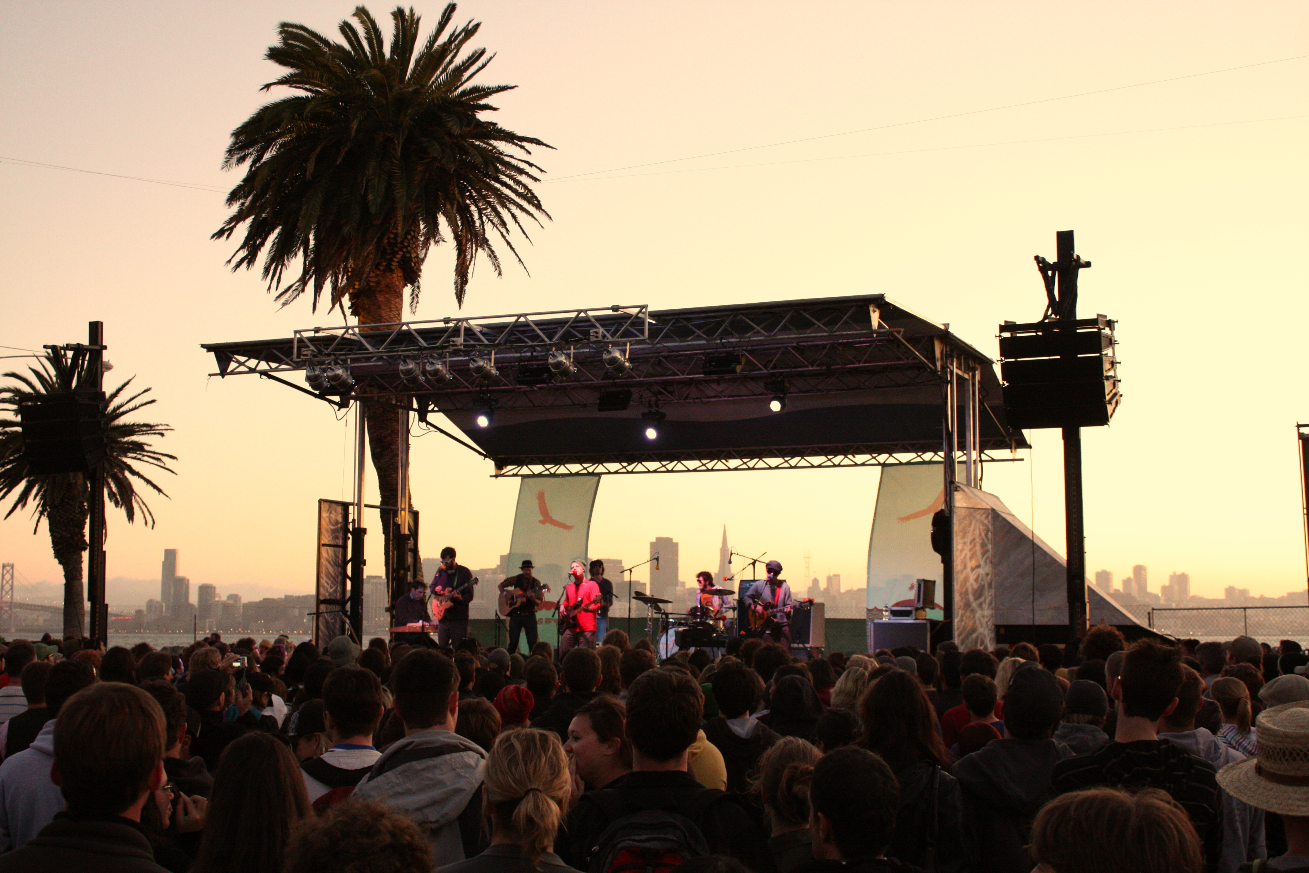 A band playing onstage at Treasure Island, with the San Francisco skyline silhouetted in the sunset behind them.