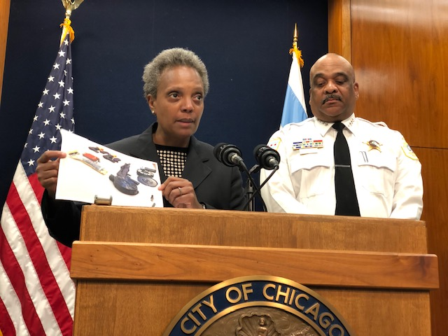 Mayor Lori Lightfoot holds up a photo of automatic weapons and high-powered ammunition seized from offenders on Friday night who were subsequently released on $10,000 bail. Police Supt. Eddie Johnson is on the right.