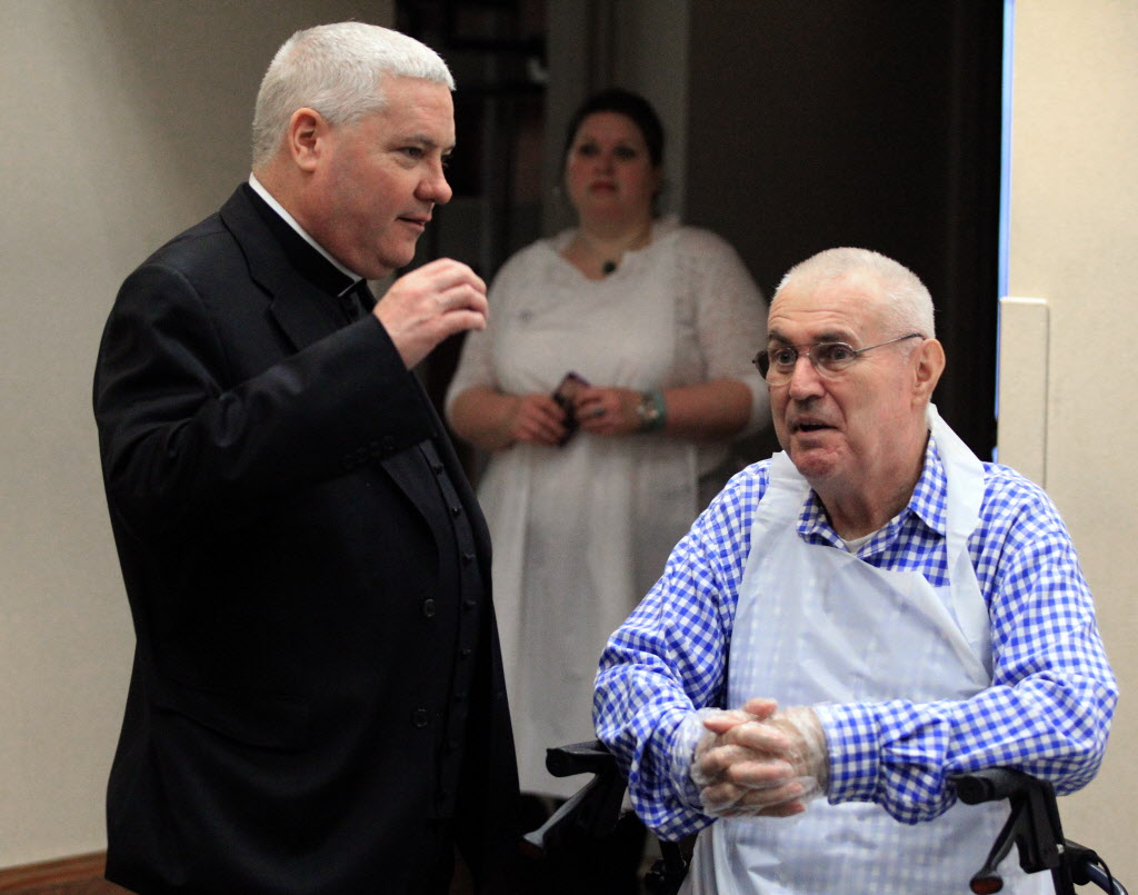 Monsignor Michael Boland talking with a volunteer at a Thanksgiving meal in 2015, will step down from his position at Chicago Catholic Charities' CEO on Aug. 16.
