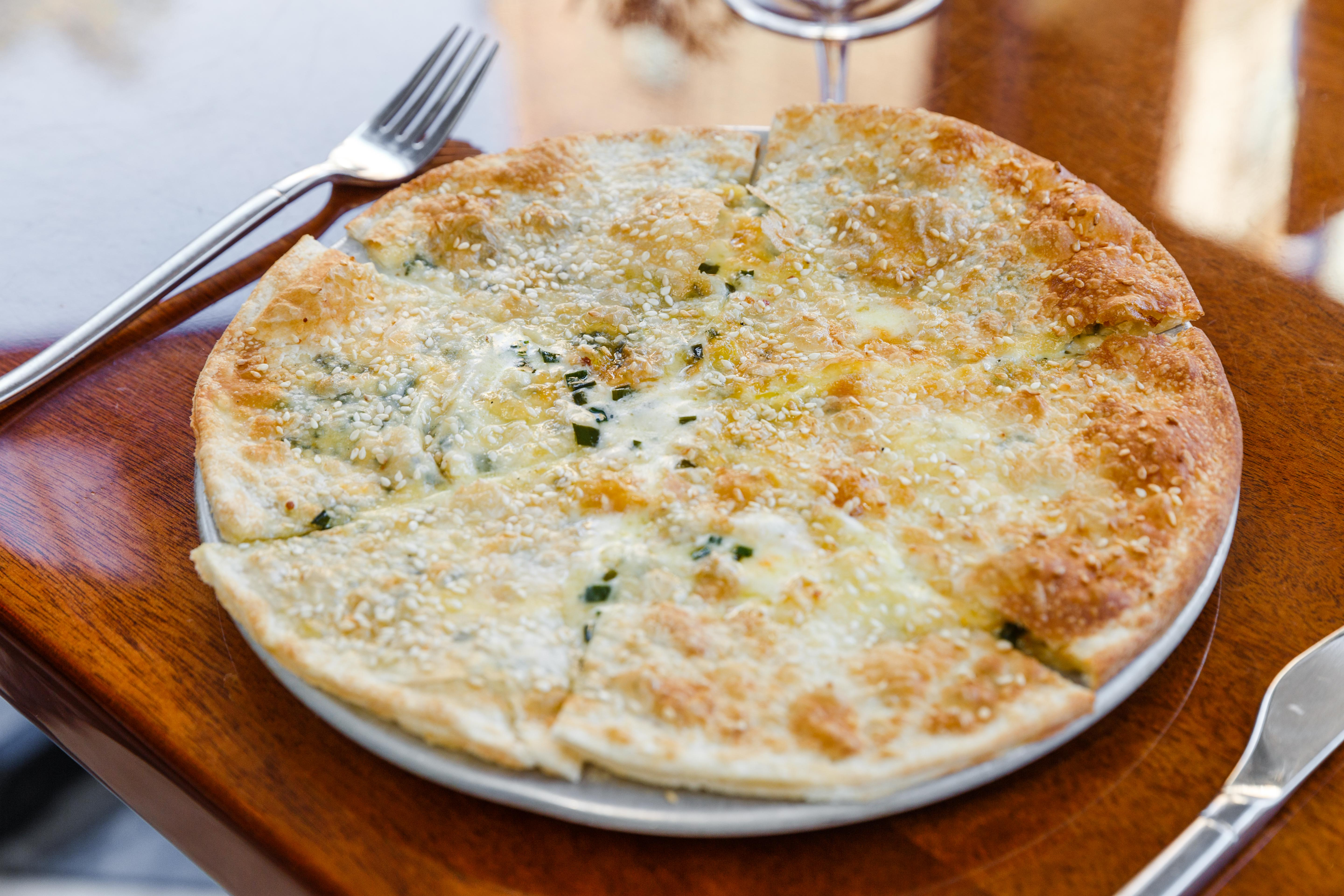 A round, sesame-studded flatbread is cut up into slices on a big plate on a reddish wooden table.