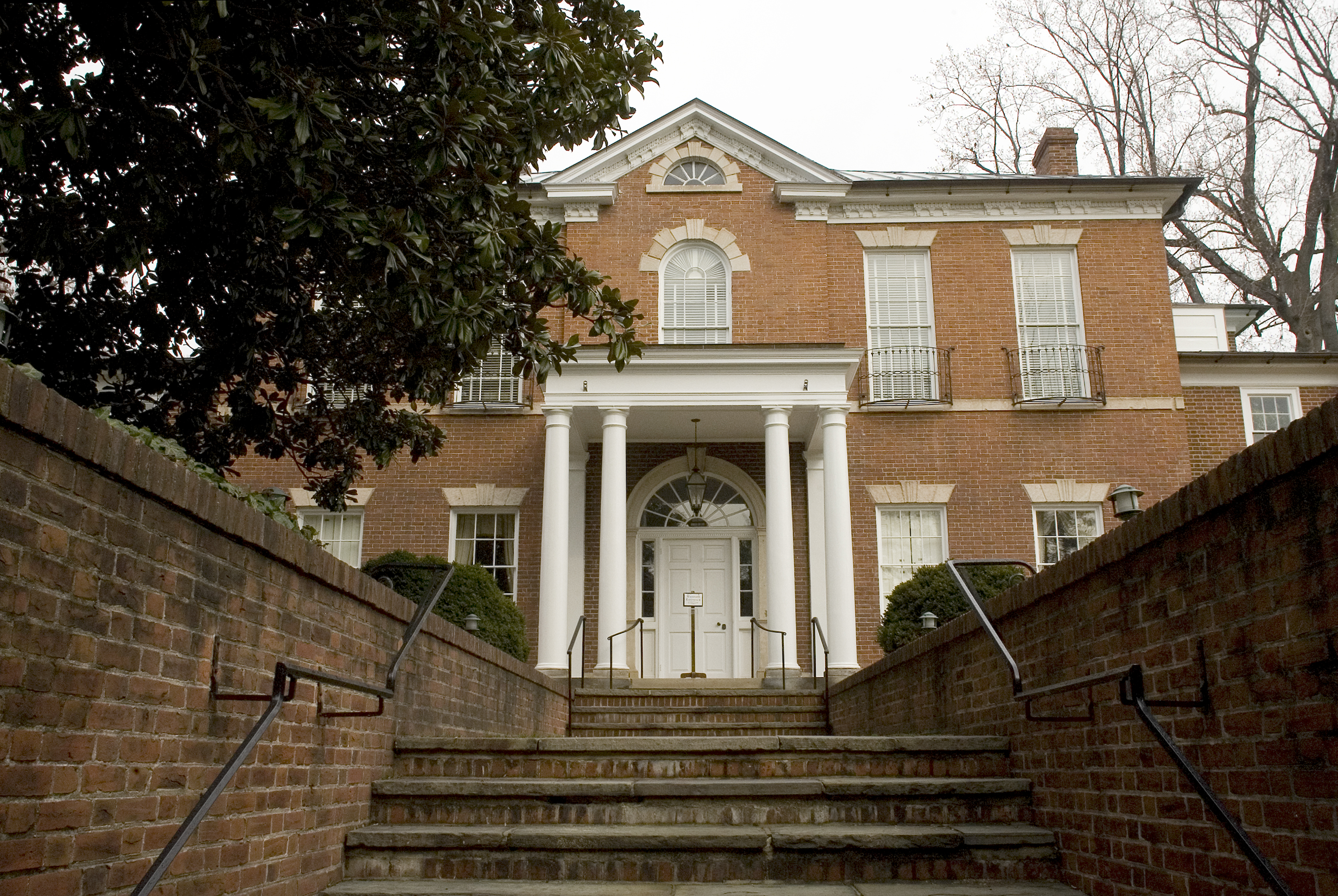 Dumbarton House, a Federal style building in Georgetown, as seen from the front. There are stairs leading up to the brick facade and white columns.