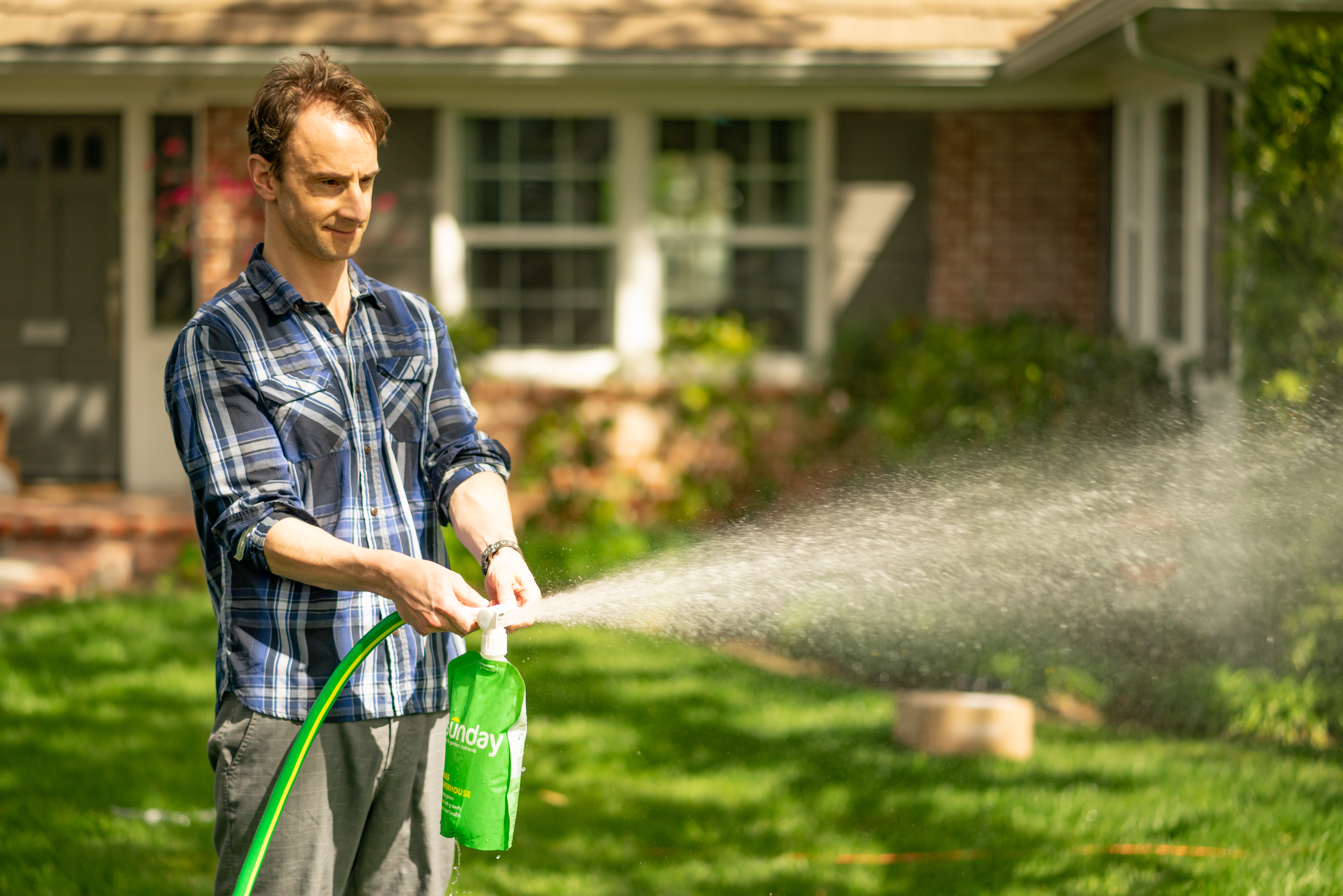 A man spays his lawn with a green pouch of fertilizer.