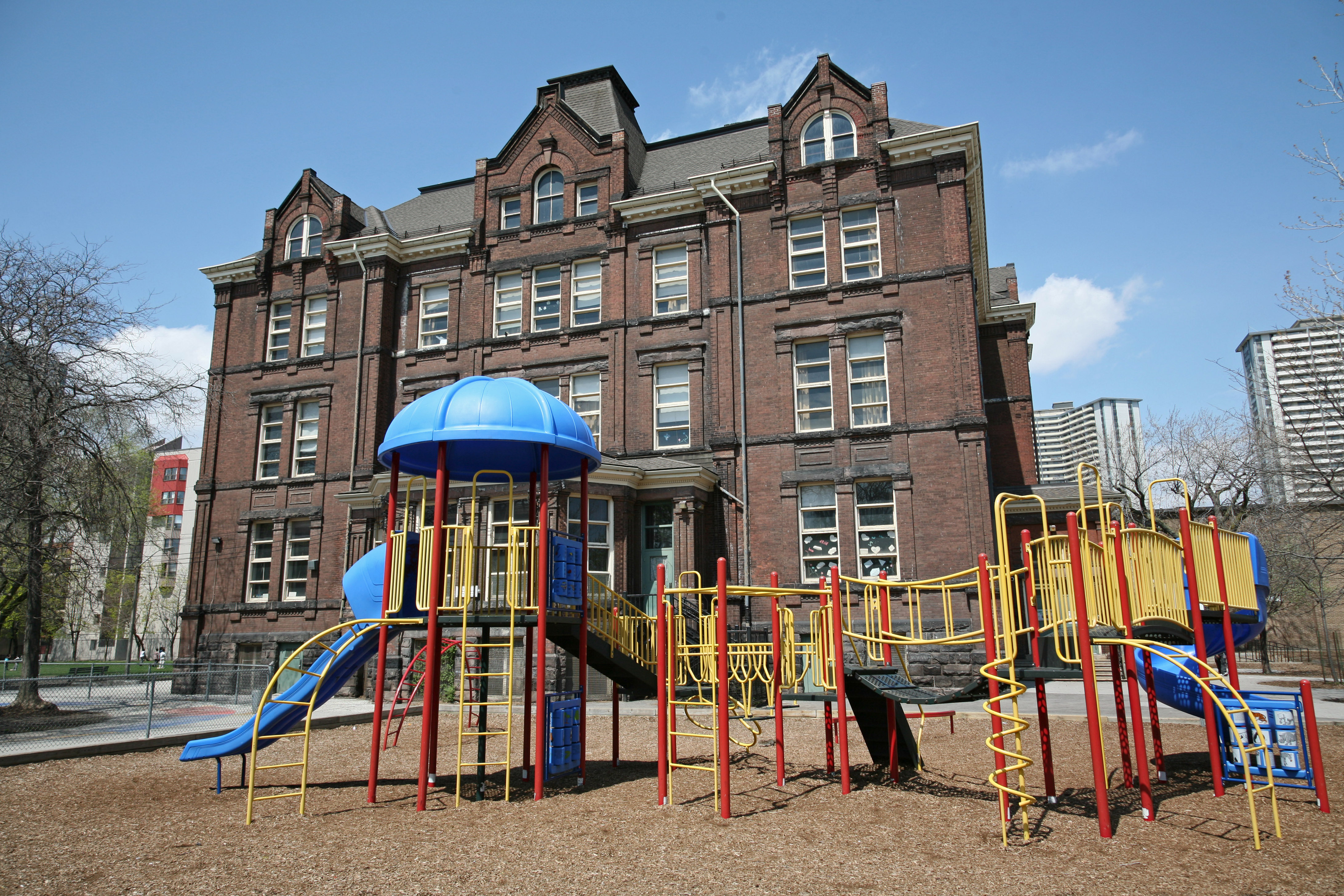 A colorful playground setup in front of an old brick school building.