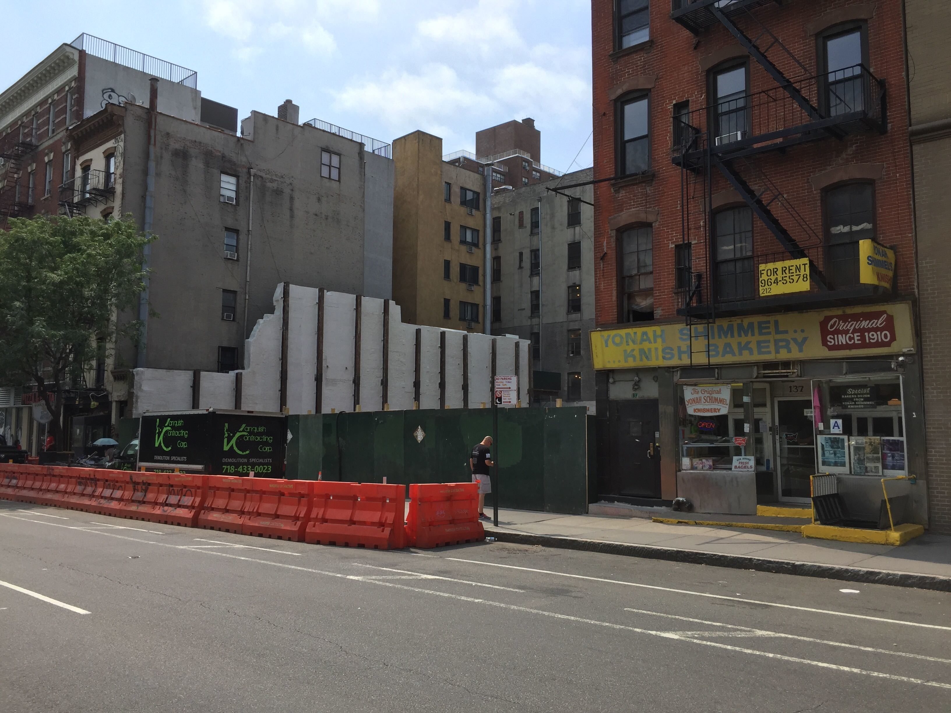 On East Houston Street, in the Lower East Side, a construction site next to a three story building.