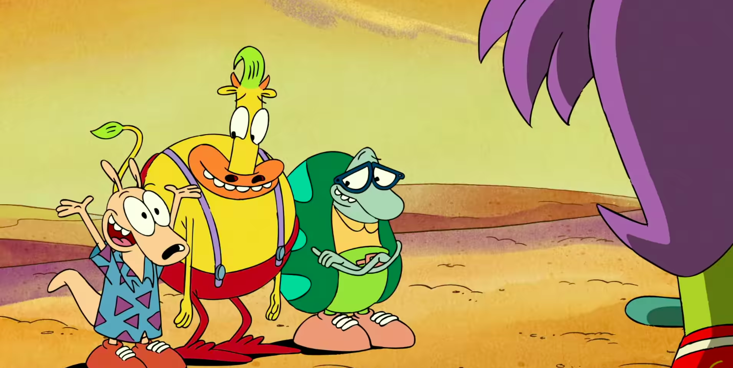 Three anthropomorphic animals — a wallaby, a cow, and a turtle — stand on a sandy background. They are Rocko, Heffer, and Filburt of Rocko's Modern Life. The outline of someone's face and hair can be seen in the right corner of the screen.
