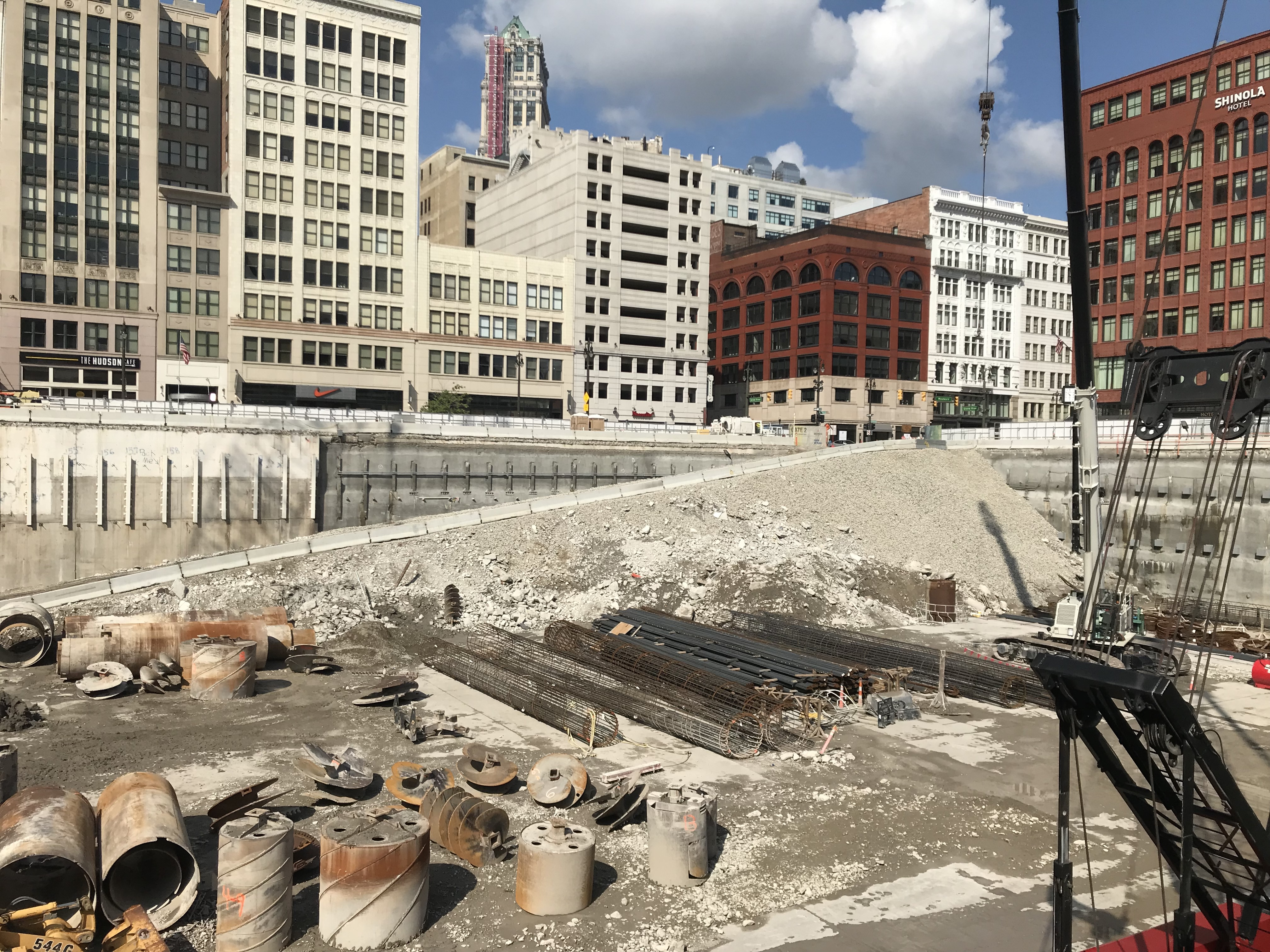 Heavy machinery and equipment in a 40-foot deep excavation site. On the other side of the hole, there's a row of 5- to 10-story buildings.
