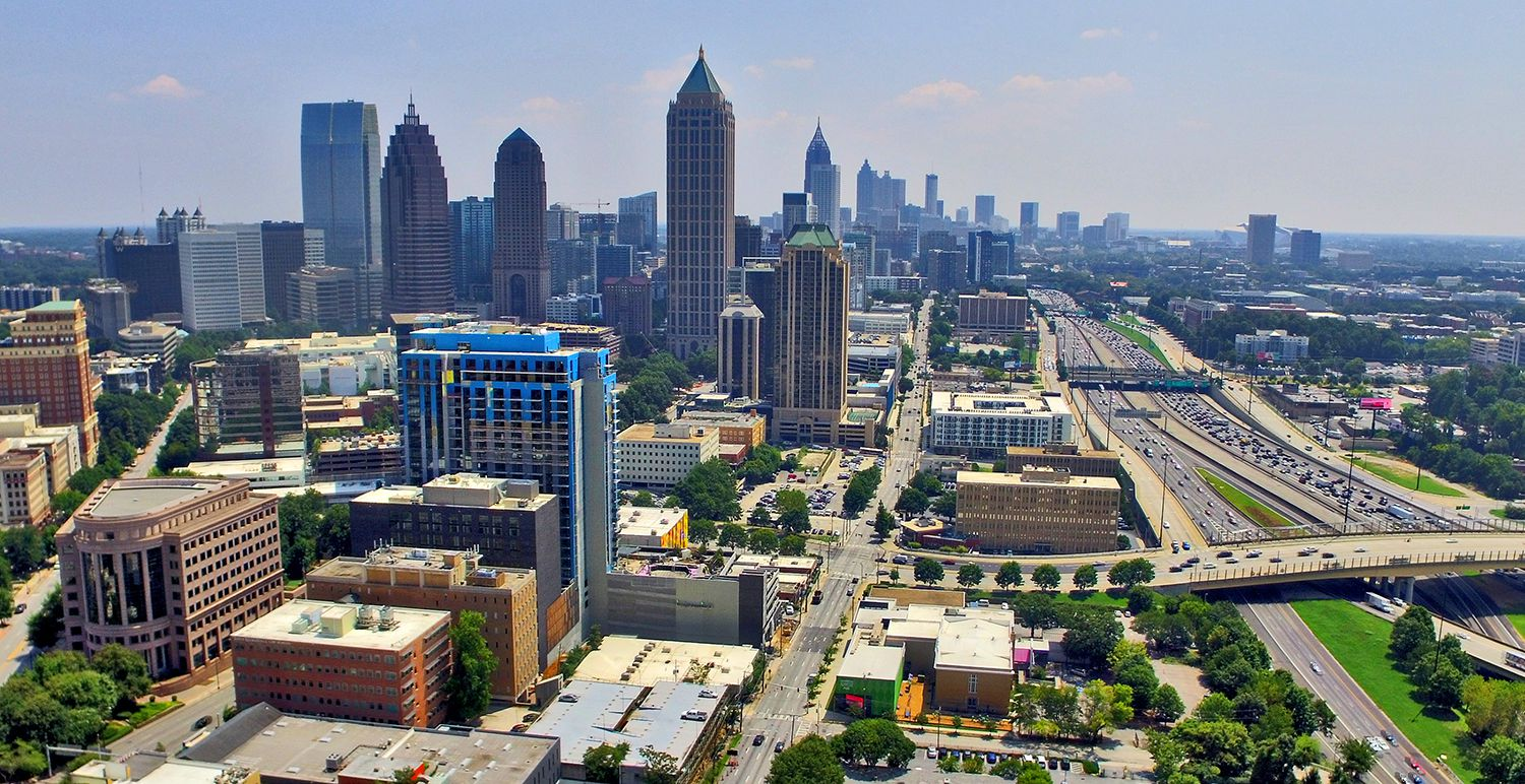 Aerial view of Midtown Atlanta, with a skyline at left and the highway to the right.