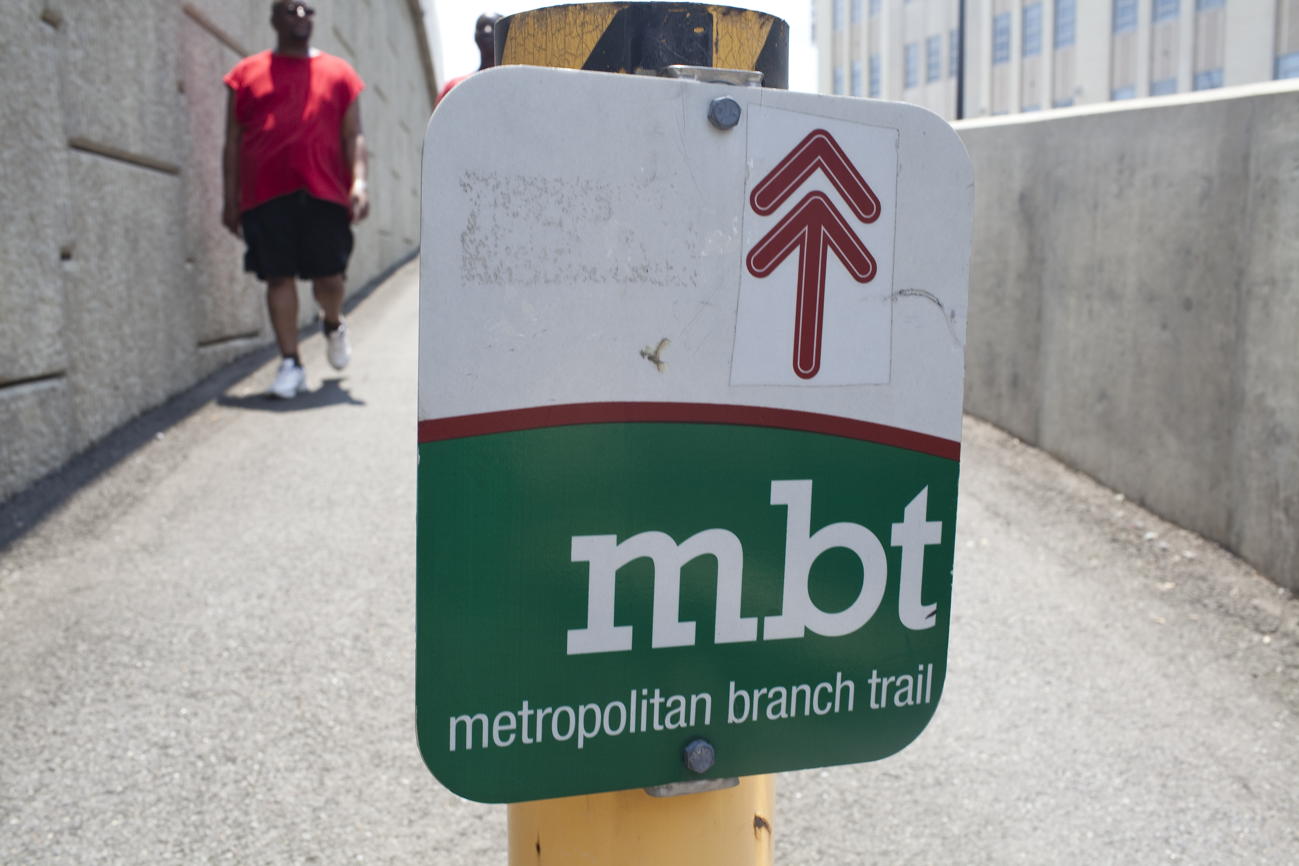A green and white sign for the Metropolitan Branch Trail near the NoMa–Gallaudet Metro station. A man wearing a red t-shirt and shorts is seen walking behind the sign.