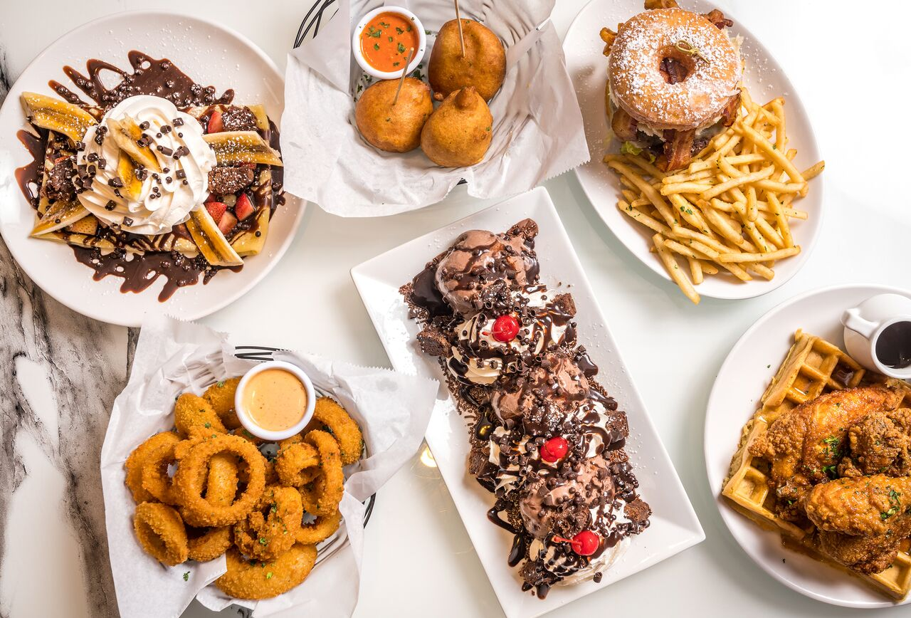 A plate of banana split crepes covered in chocolate, fried doughnut sandwich with fries, onion rings, fried mac and cheese poppers, a large chocolate sundae, and chicken and waffles