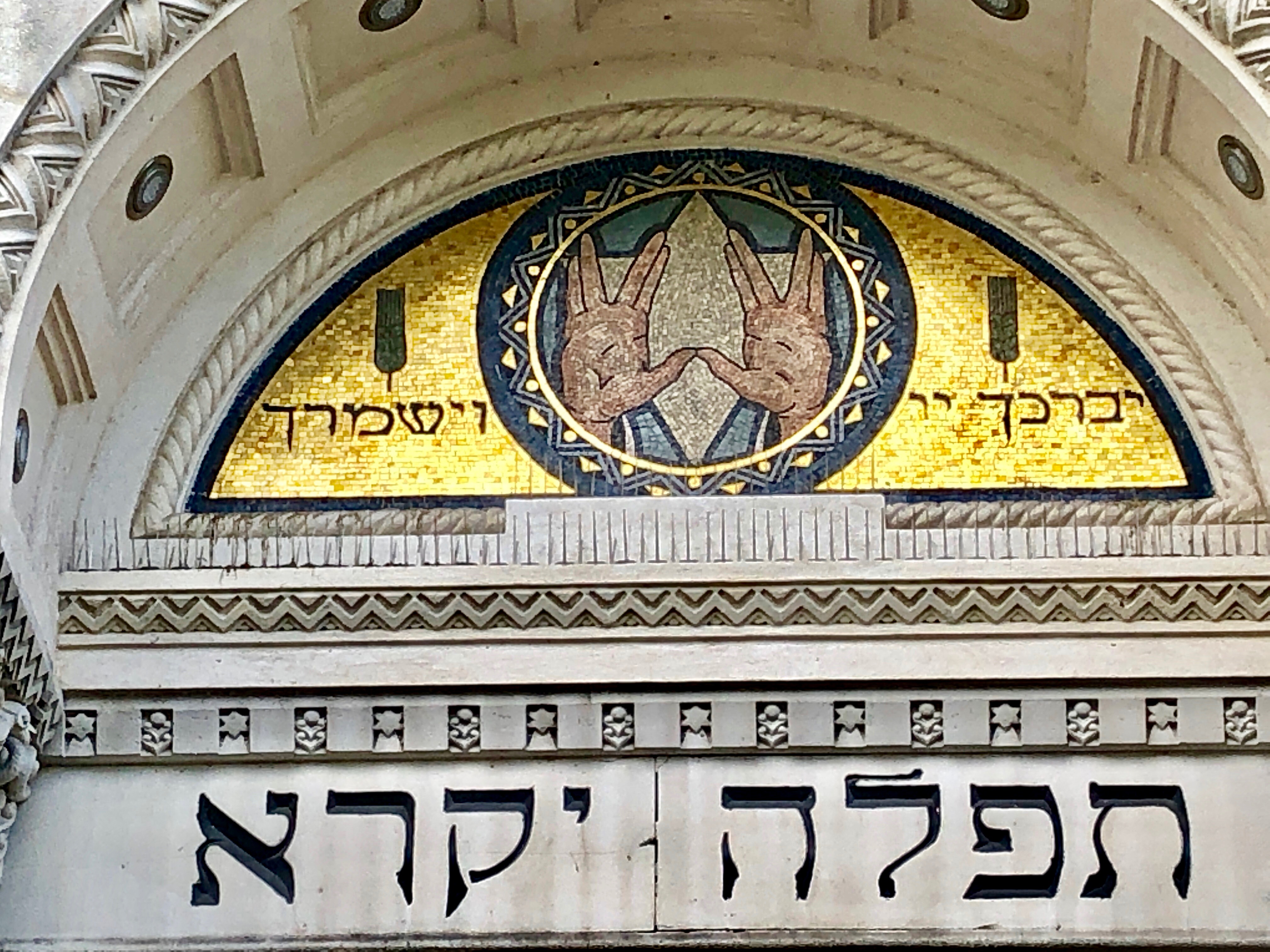 A pair of outstretched hands against a gold tile background above Hebrew letters.
