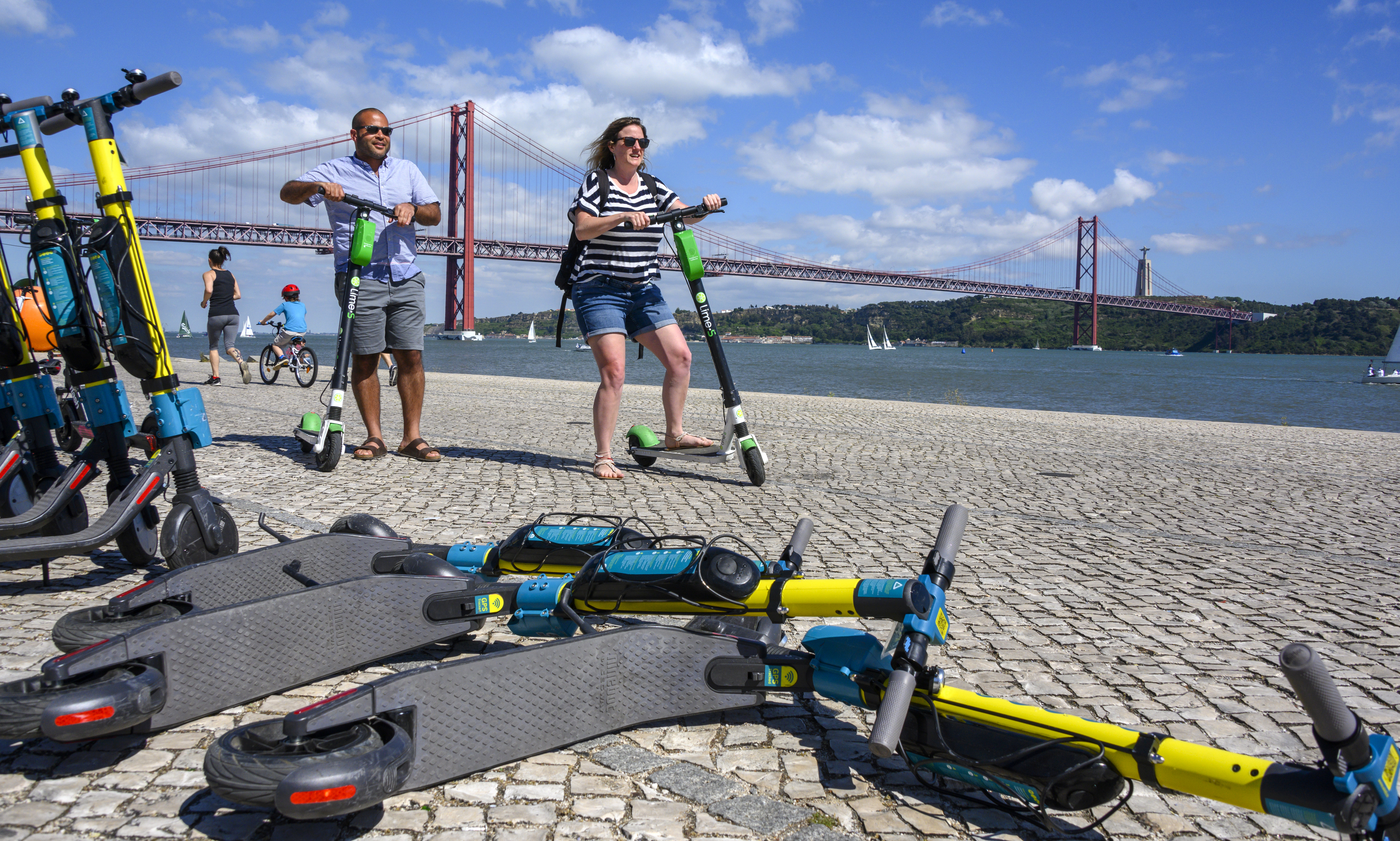 People using Lime e-scooters in Lisbon, Portugal.