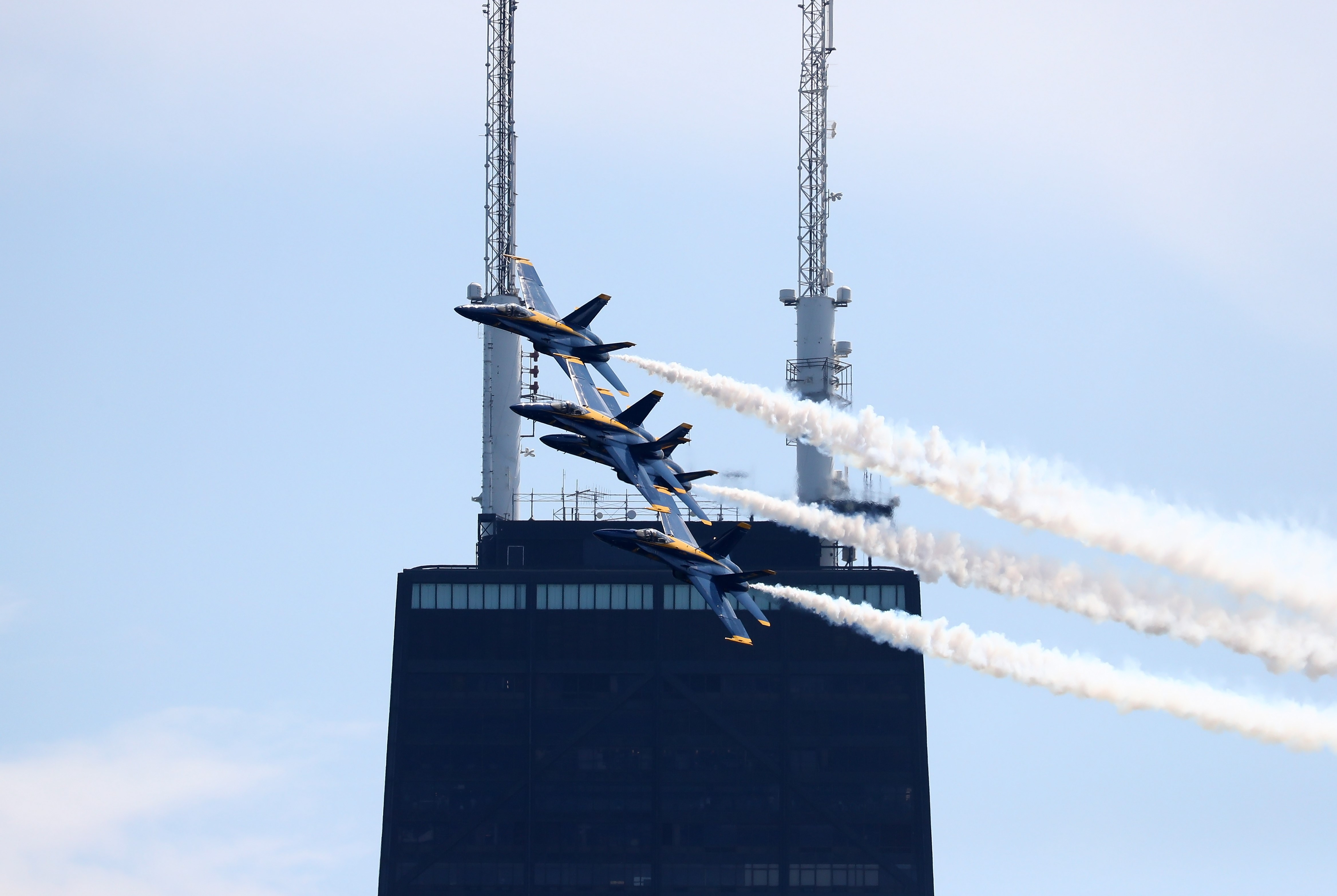 Four Blue Angel F-18 jets fly in a diamond formation front of the twin antennas of John Hancock Center.