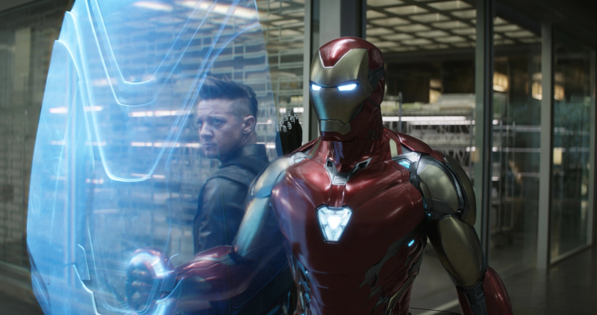 Iron man, in a red and gold suit with a glowing heart-shaped arc reactor, projects a blue shield. Hawkeye is in the background. They are in a lab.