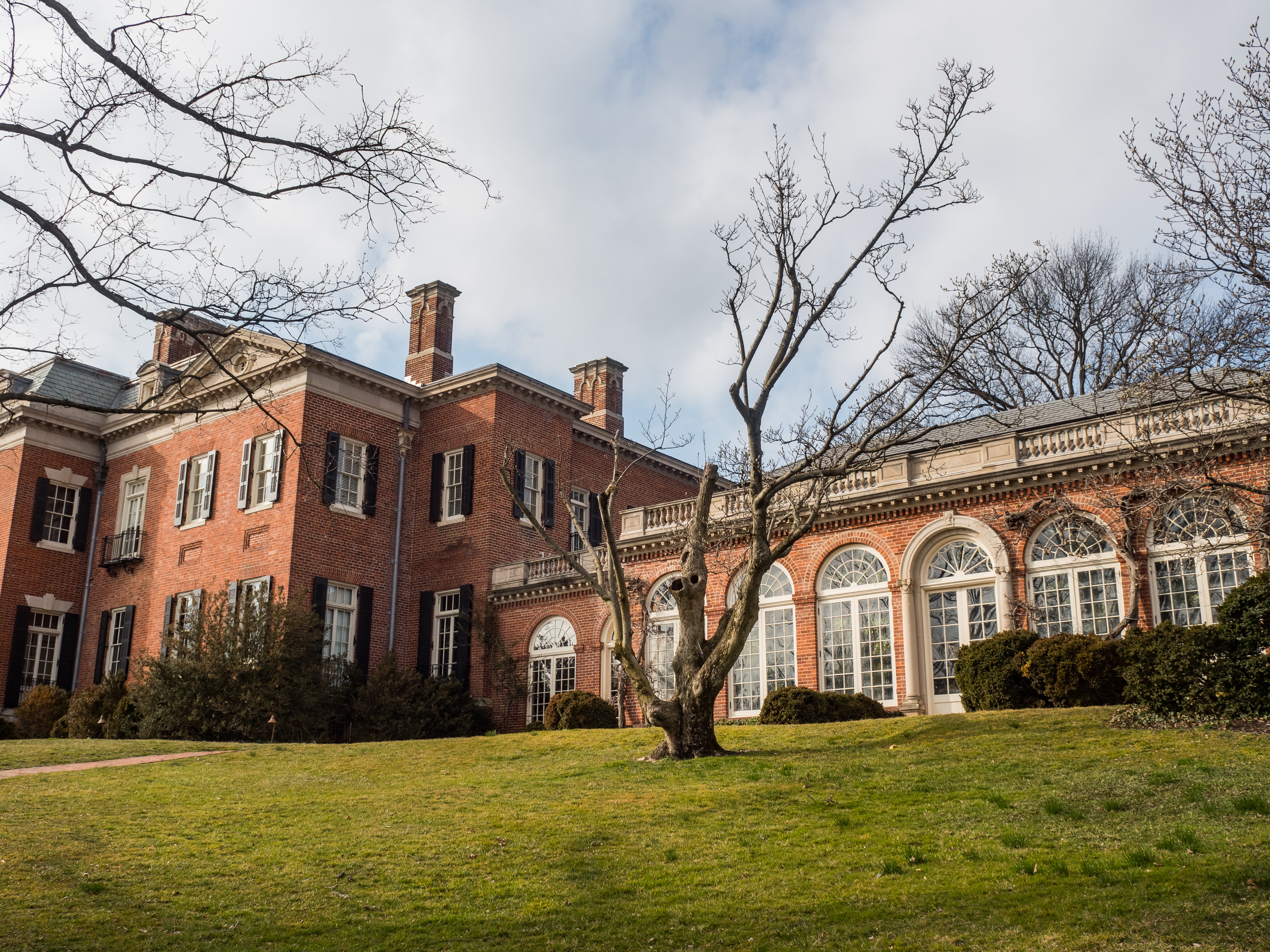 The Dumbarton Oaks estate in Georgetown, an elaborate mansion made of brick. Large windows line a wing of the estate.