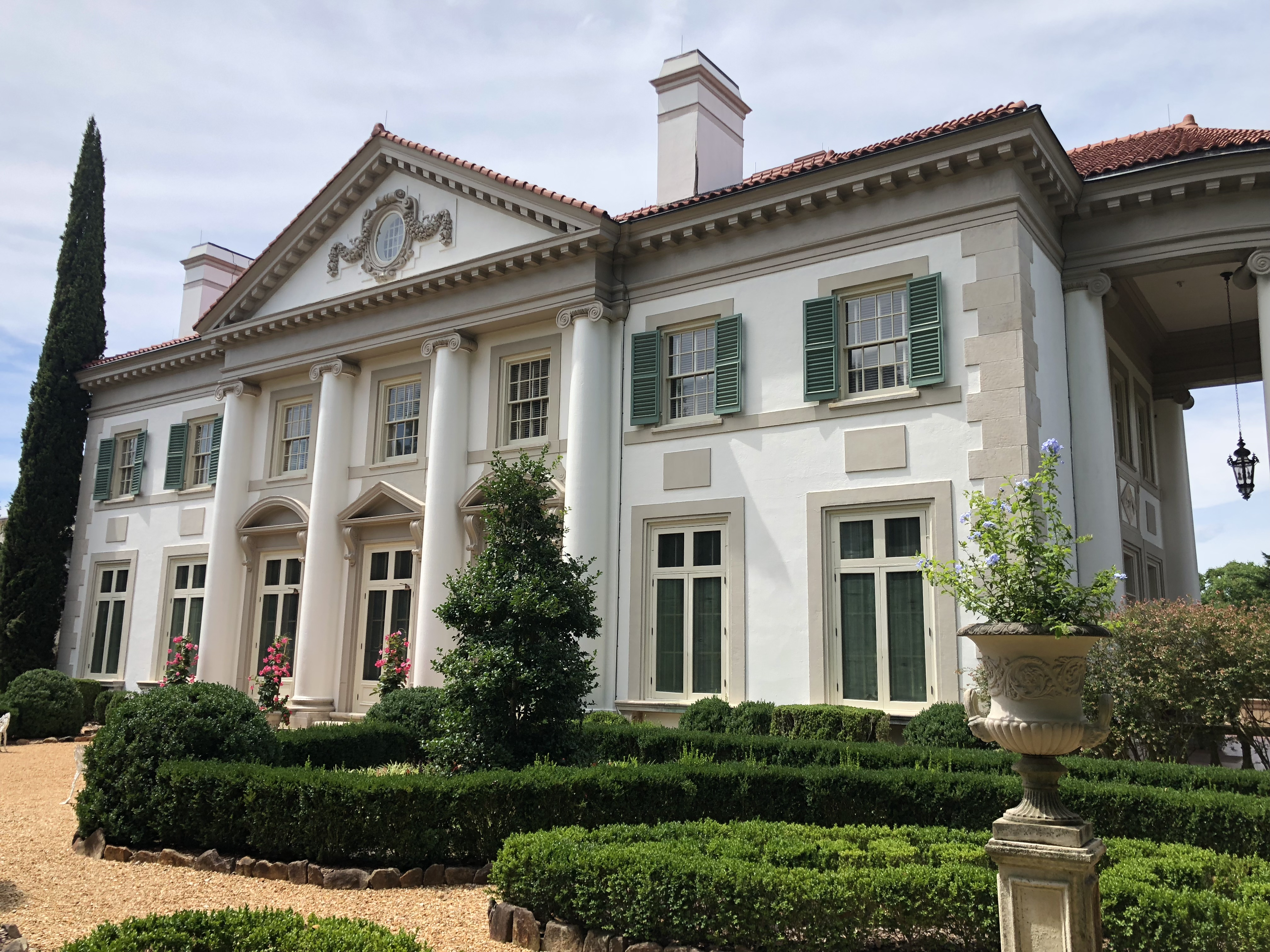 Three-story house with four columns and lots of windows.