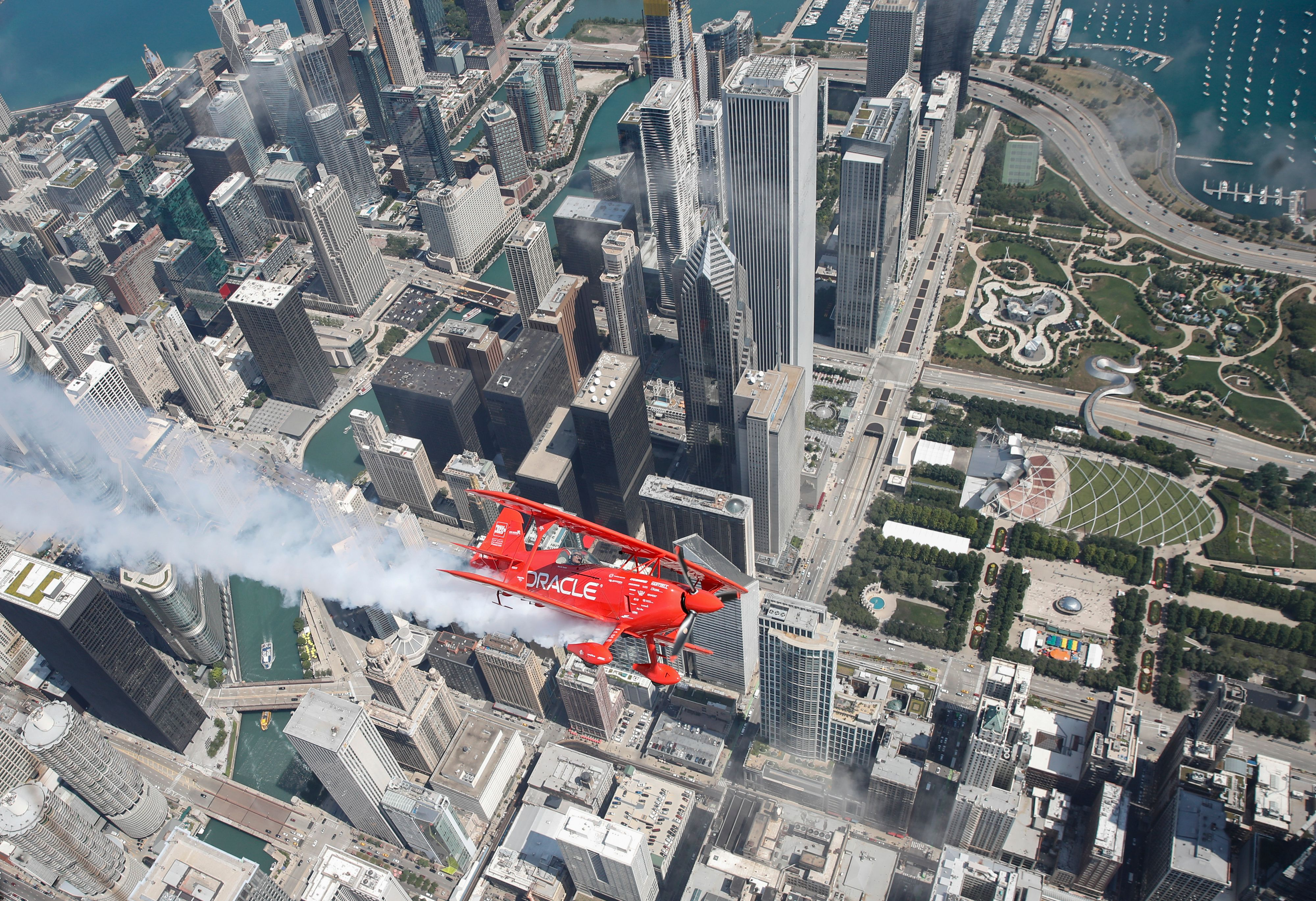 A red biplane leaves a fluffy smoke contrail as it flies over downtown Chicago. Tall buildings, a blue lake, and a green park are visible below.