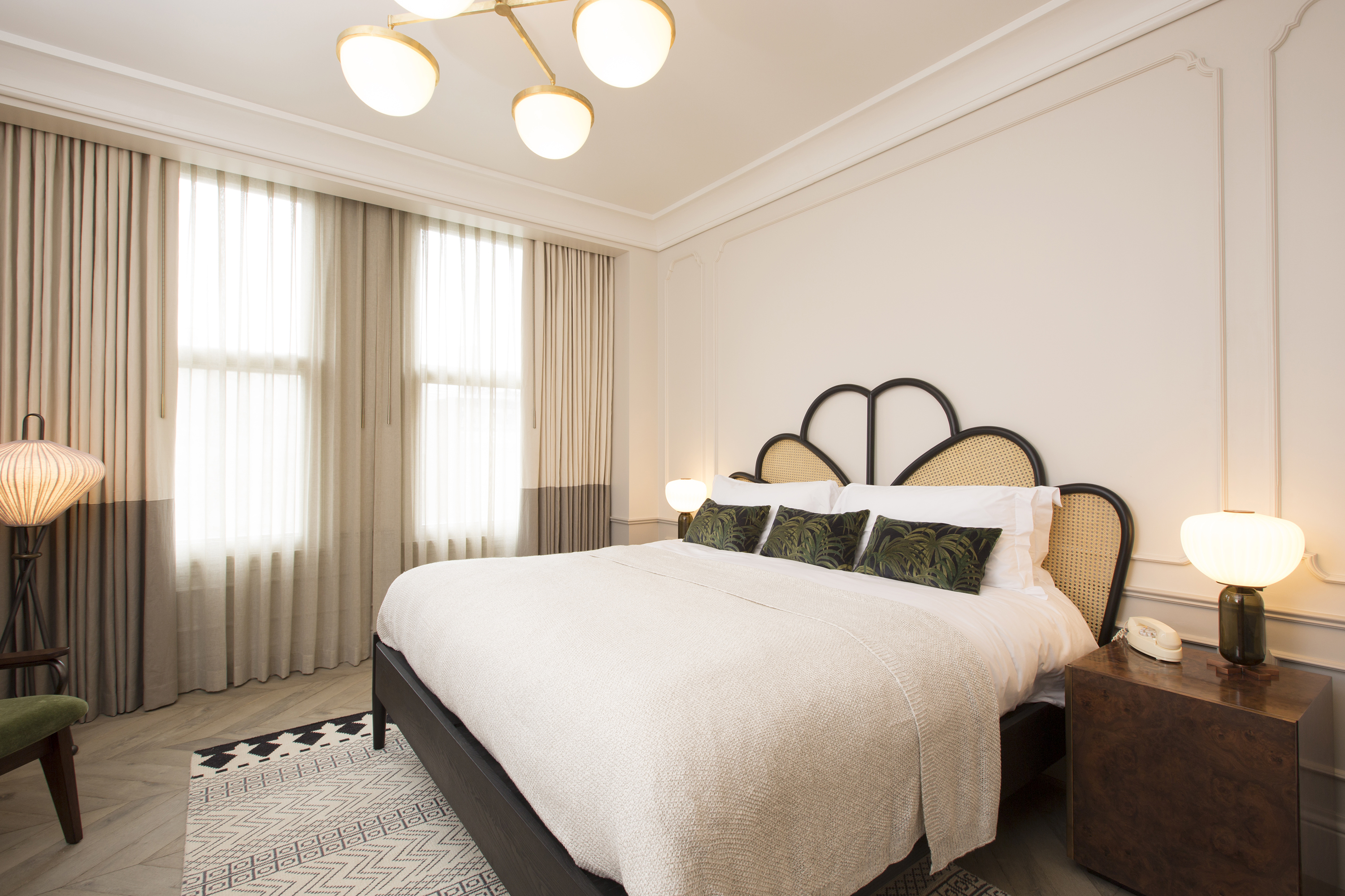 A photo of a bright, white bedroom with crown moldings, a queen-size bed with headboard, and chandelier-style lighting fixture with white glass globes.