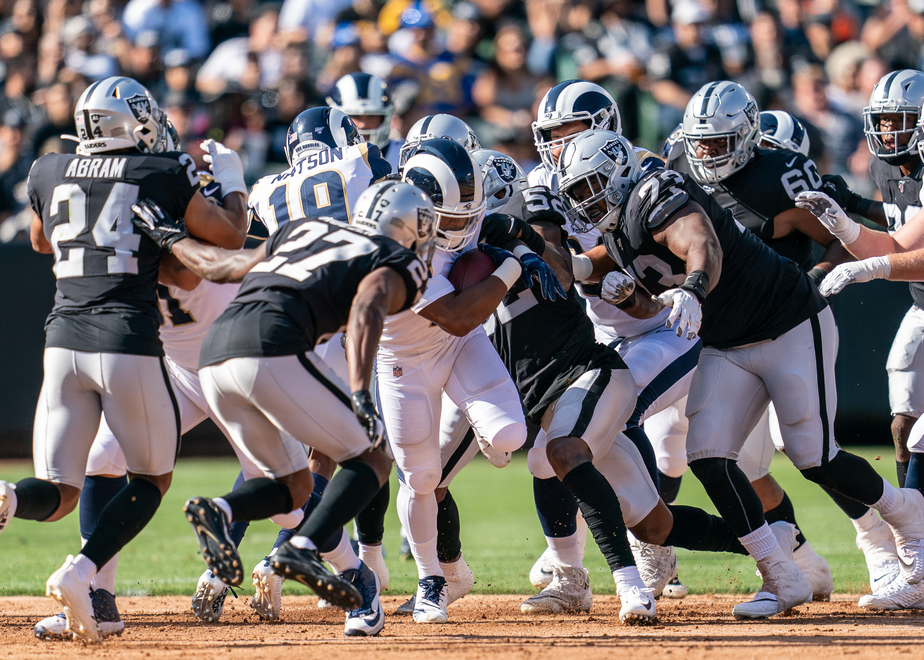 Los Angeles Rams RB John Kelly is tackled by Oakland Raiders CB Trayvon Mullen and DT Maurice Hurst, Aug. 10, 2019.