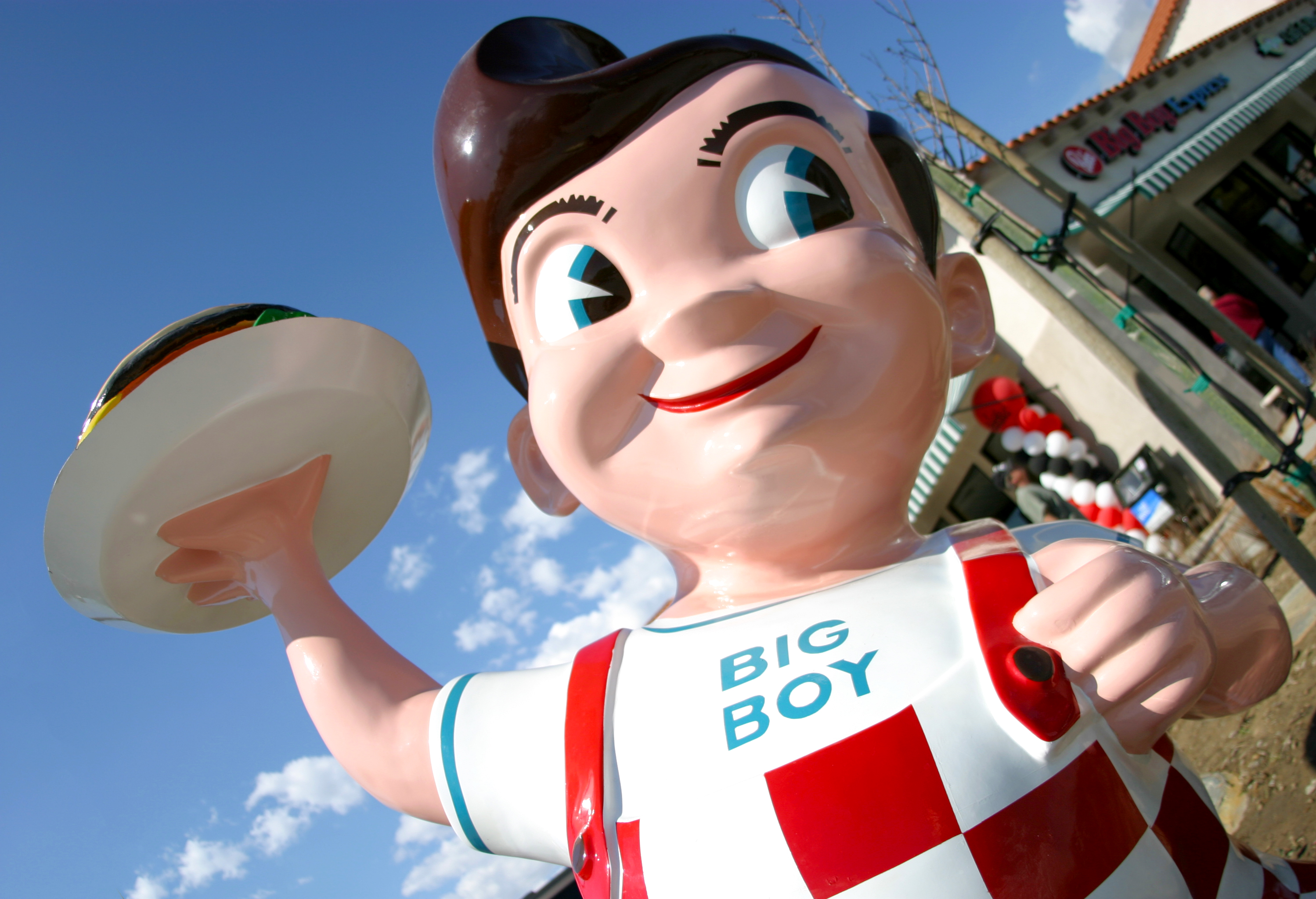 a massive big boy sculpture outside of a restaurant.. He has brown hair, big blue eyes, checkered overalls, and is holding a burger on a plate in one lifted hand.