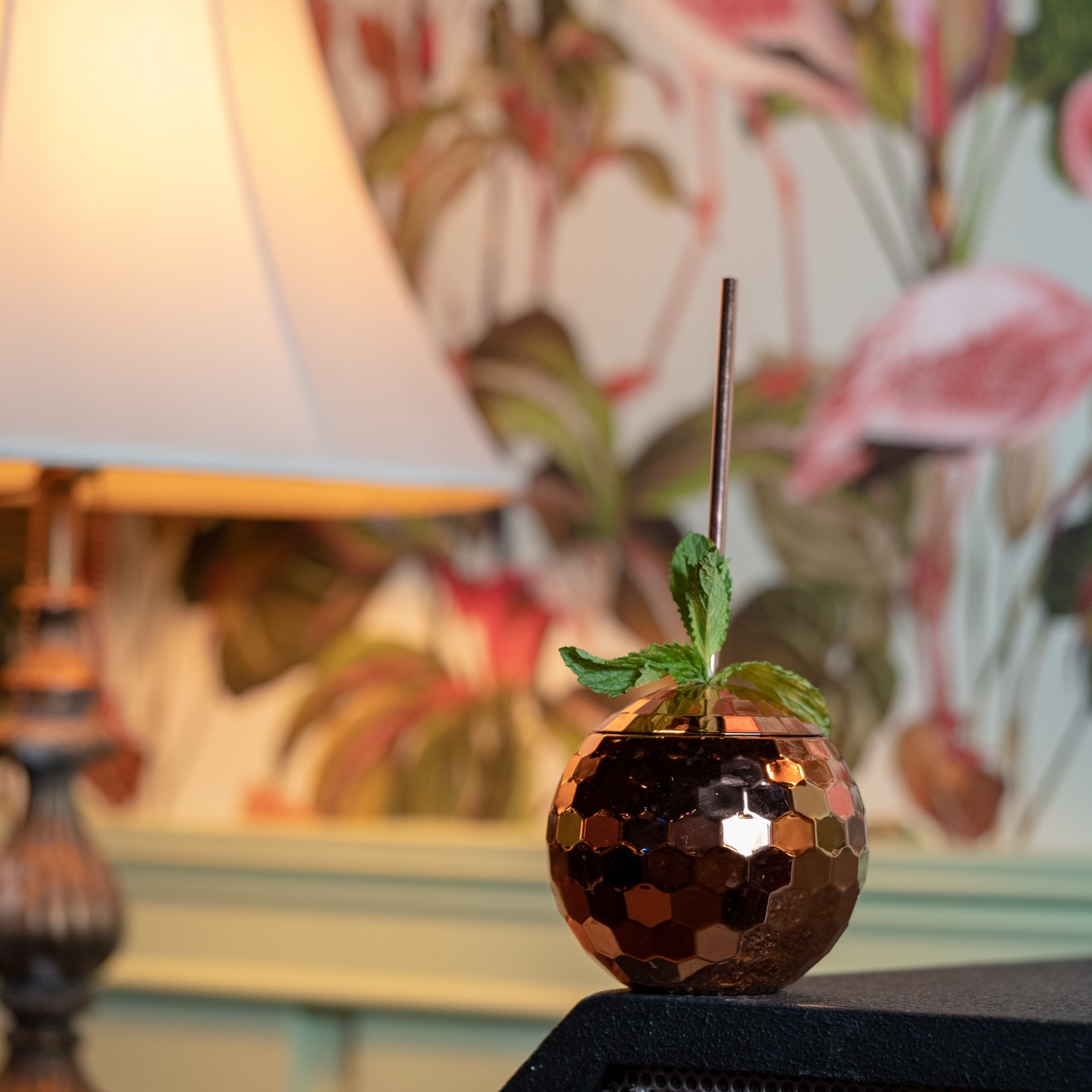 A disco ball cup with a metal straw on a table in front of a floral wallpapered wall