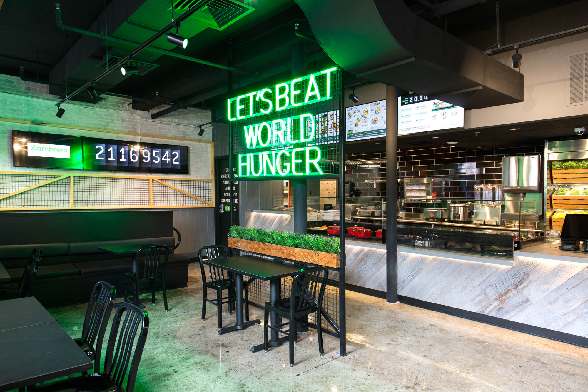 "A neon sign reading ""let's end world hunger"" hangs in front of an ordering counter inside Zambrero"