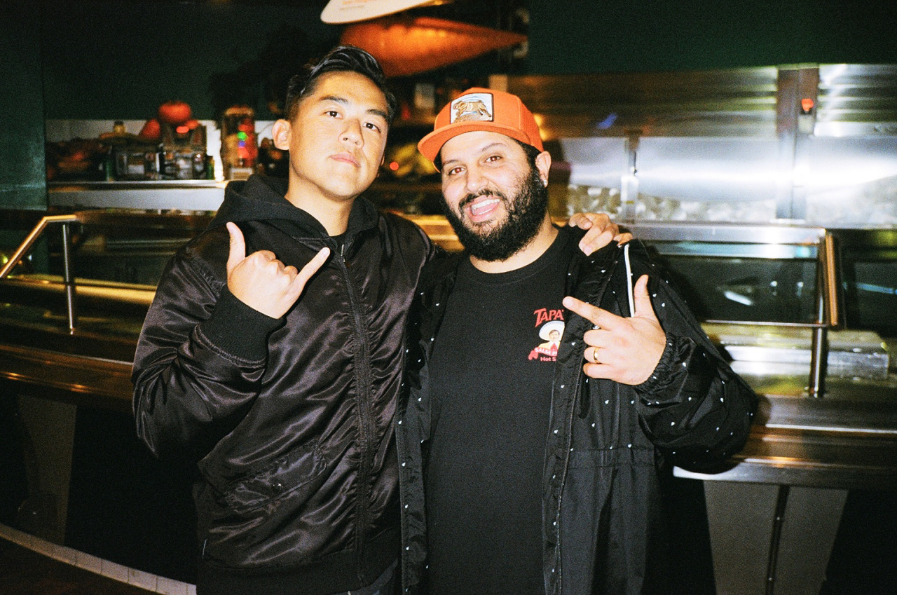 Bobby Kim and Ben Shenassafar from the Hundreds pose for a picture at a restaurant, wearing black.