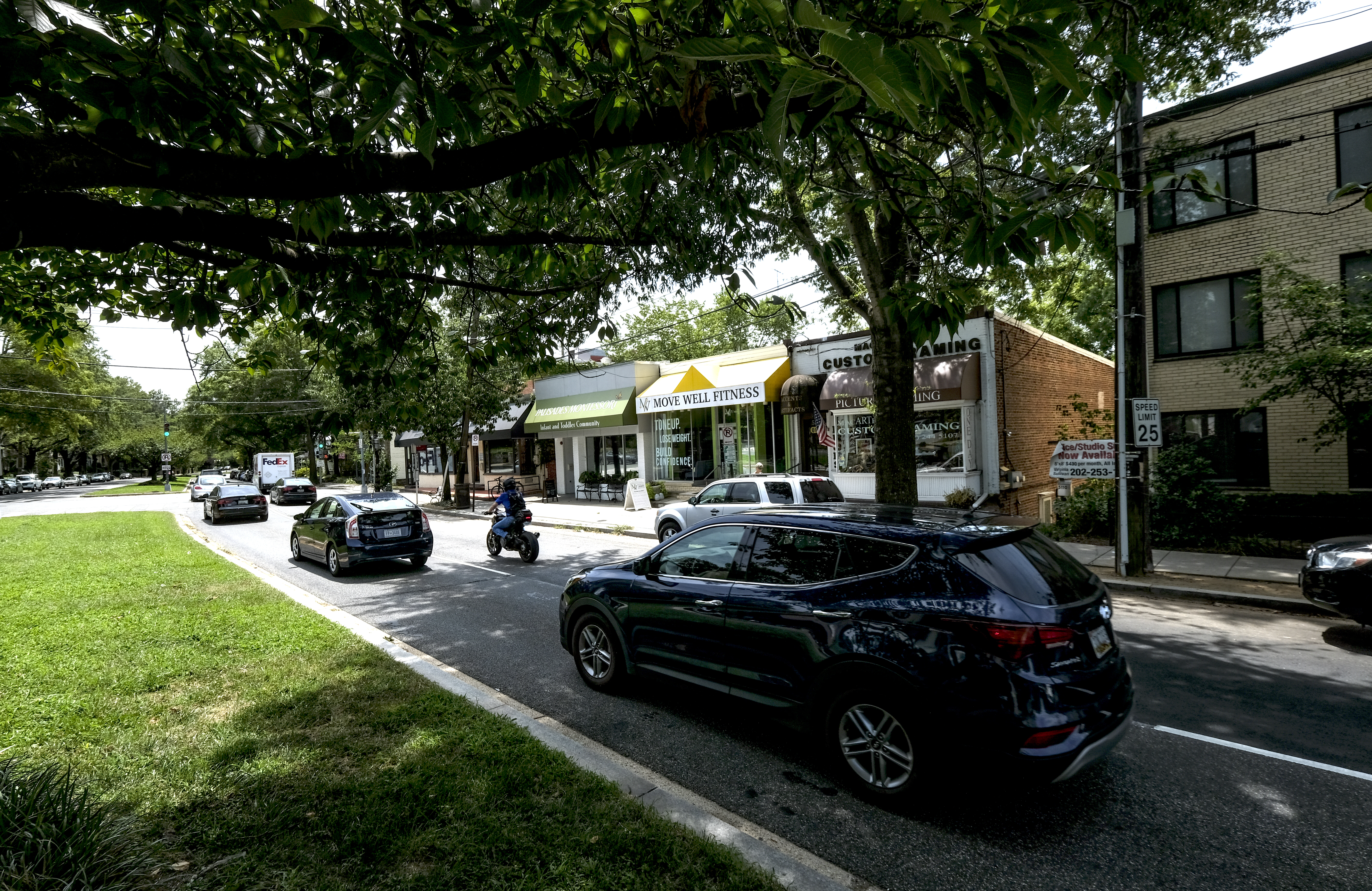 Cars travel along MacArthur Boulevard NW in D.C.'s Palisades neighborhood, with stores in the background.