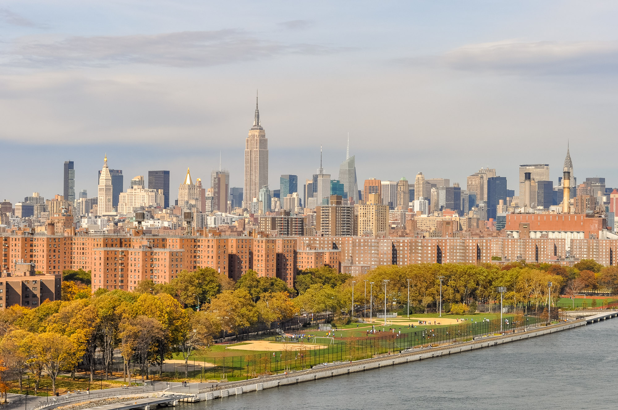 Dozens of brown public housing buildings are shown in the foreground with midtown Manhattan's skyline in the background.