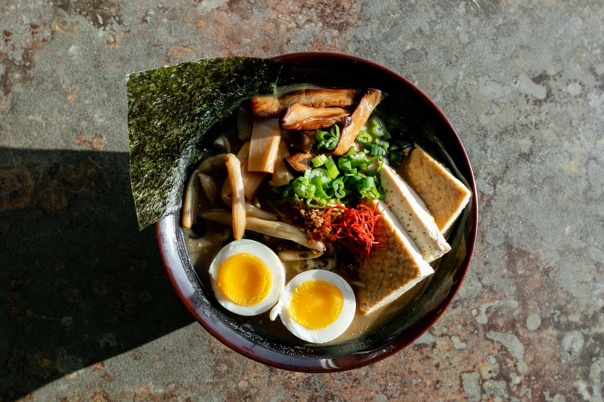 A vegetarian udon noodle bowl with tofu, seaweed, mushrooms, soft boiled eggs, and green onion