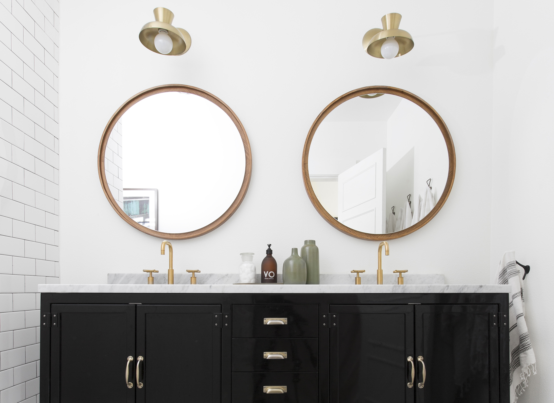 Double vanity with two round mirrors above the sinks.