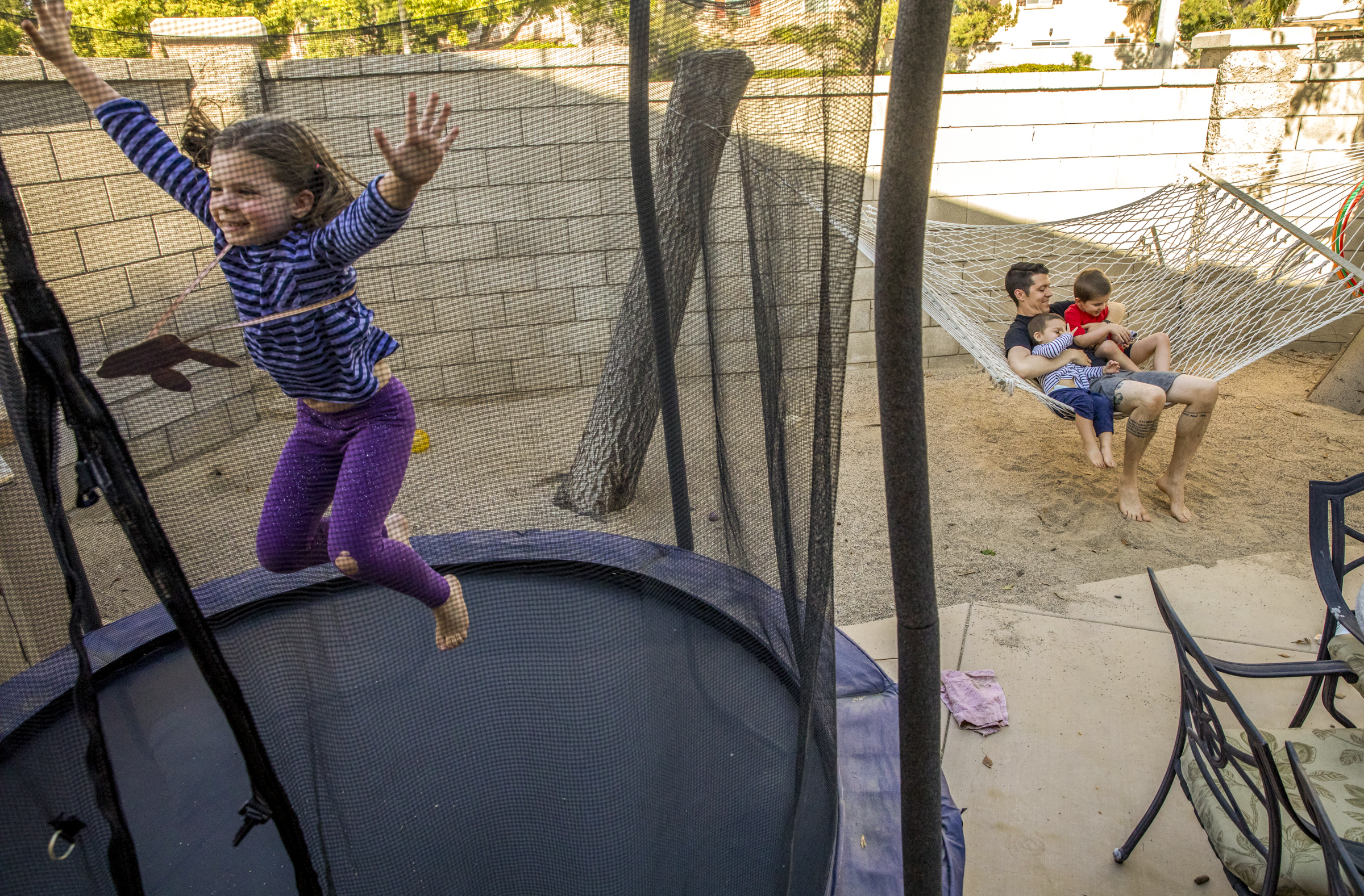 """Matt Vaudrey plays games in the backyard with his children, Cadence, 6, from left, Cameron, 2, and Clay, 4, at their home in Fontana, California, Monday, April 22, 2019. Vaudrey makes an effort to observe a """"digital Sabbath,"""" taking a break from technolog"""