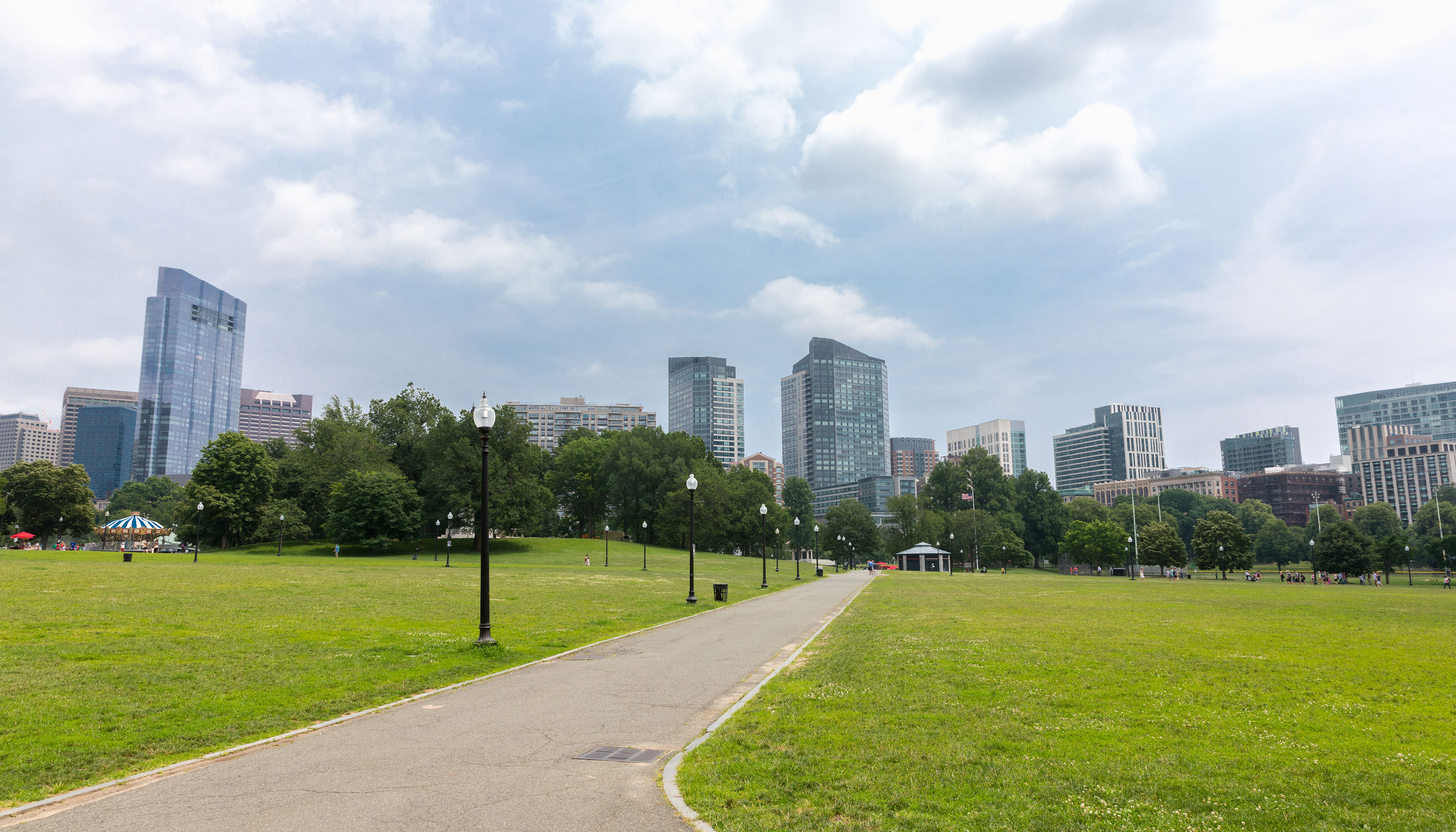 A park. There is a path that has a large expanse of green lawn on each side. In the distance is a city skyline. There is a blue sky.