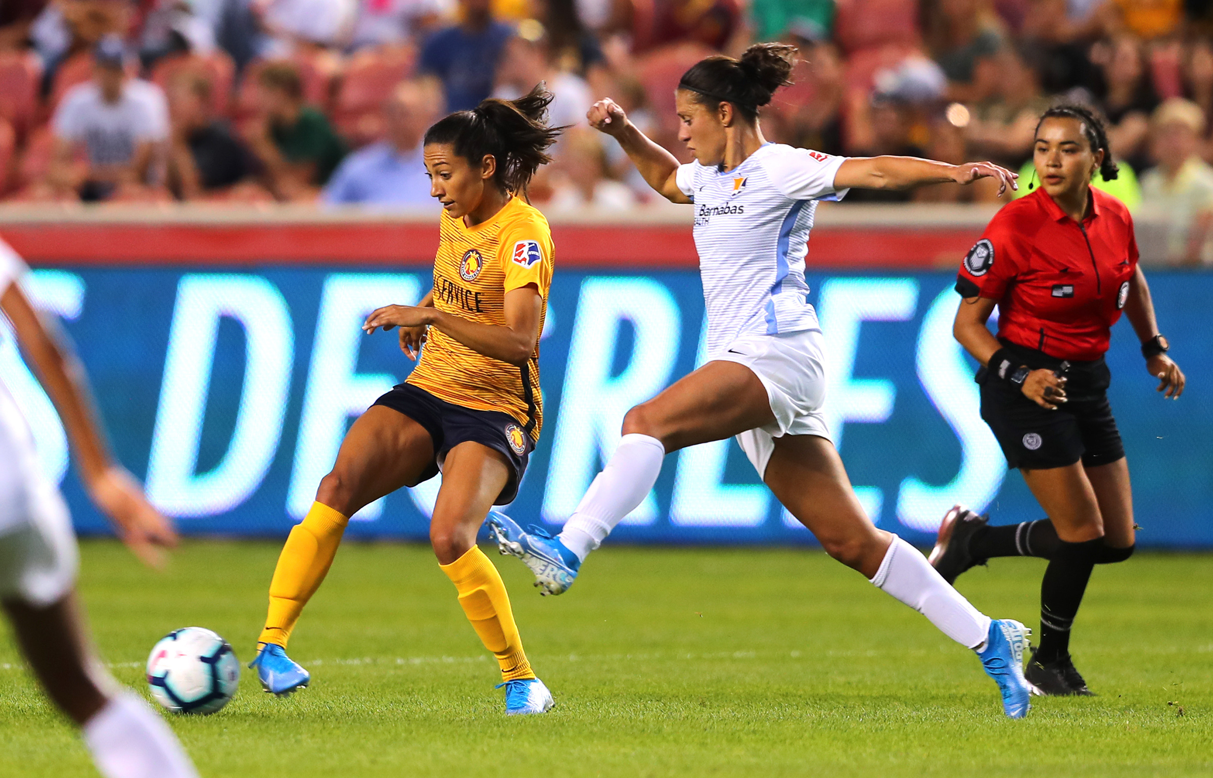 Utah Royals FC forward Christen Press (23) taps the ball away as Sky Blue FC midfielder Carli Lloyd (10) rushes in as the Salt Lake Royals and Sky Blue FC play at Rio Tinto Stadium in Sandy on Wednesday, Aug. 7, 2019.