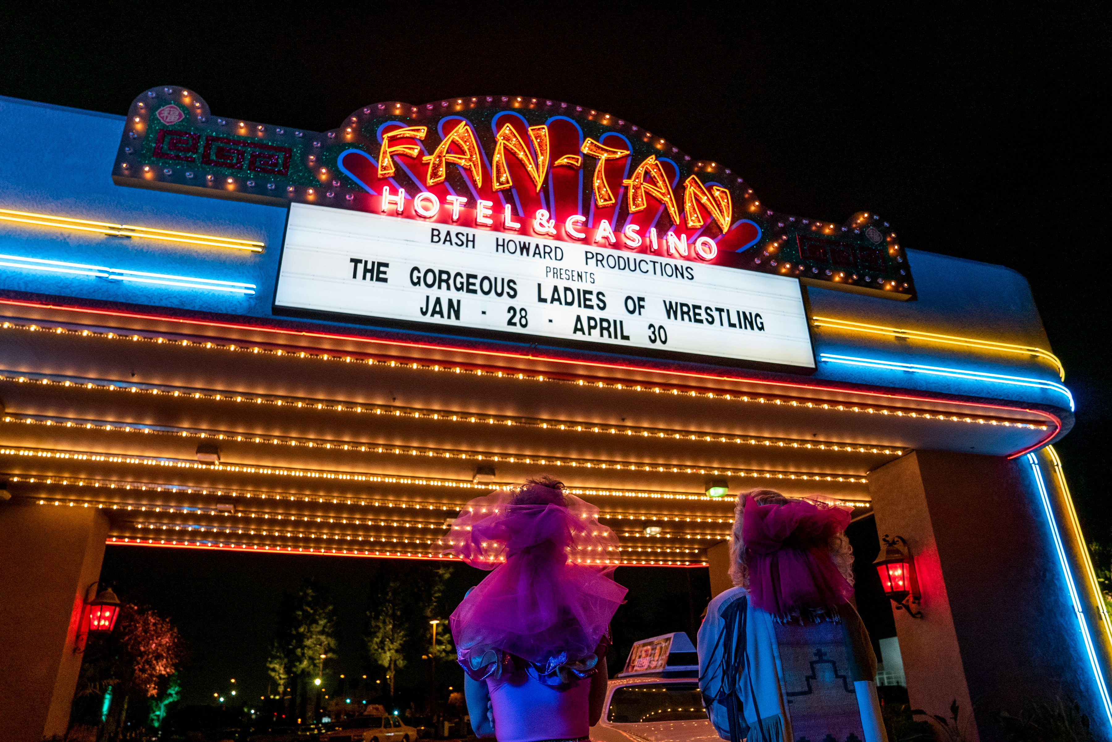 Two women of GLOW looking up at their marquee.