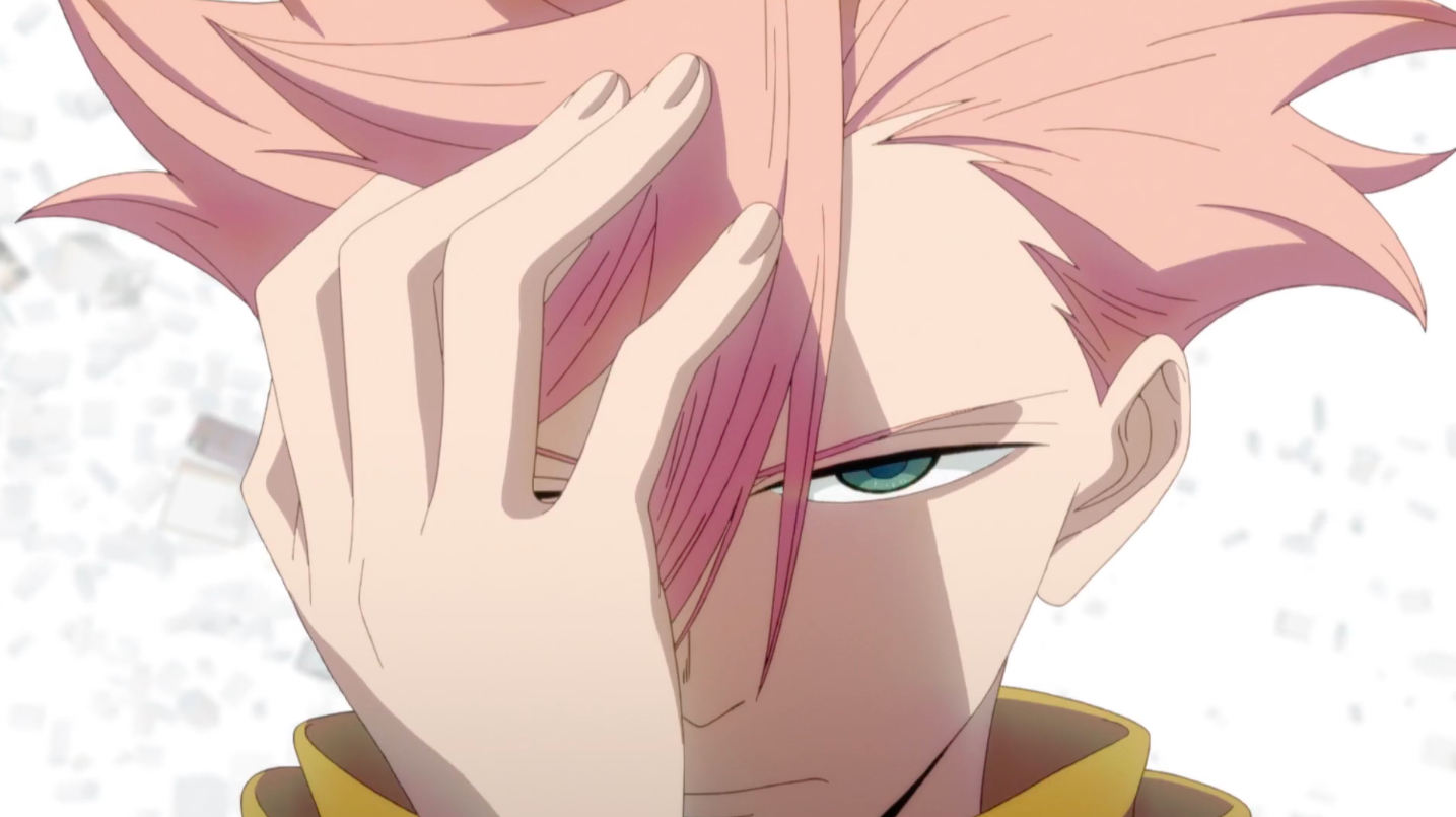 A man with pink hair covers half of his face with his hand. His uncovered eye is narrowed, his expression determined. Behind him is a white background with white, blank block shapes floating around.