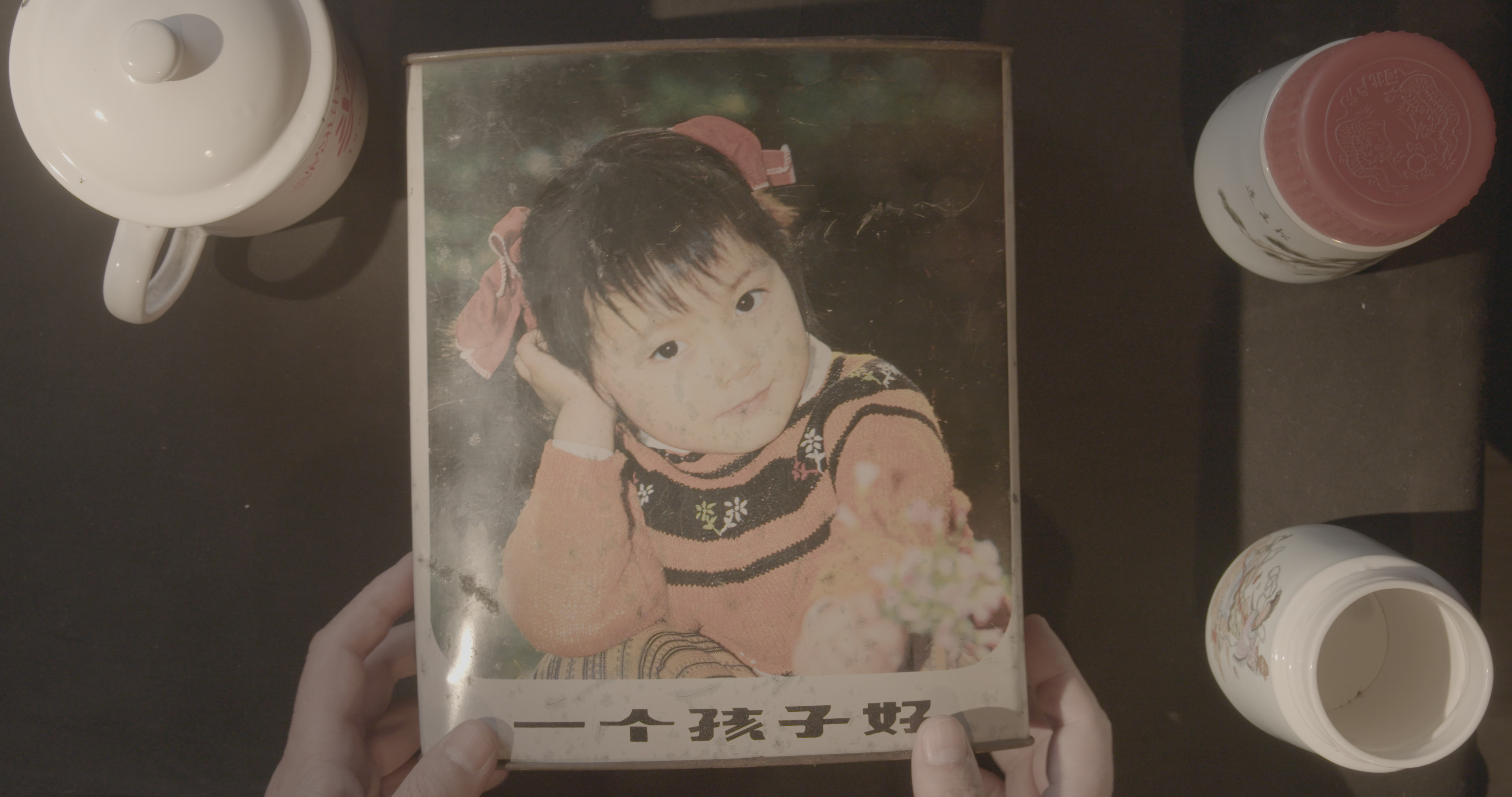 A still from One Child Nation showing a photograph of a young Chinese girl.
