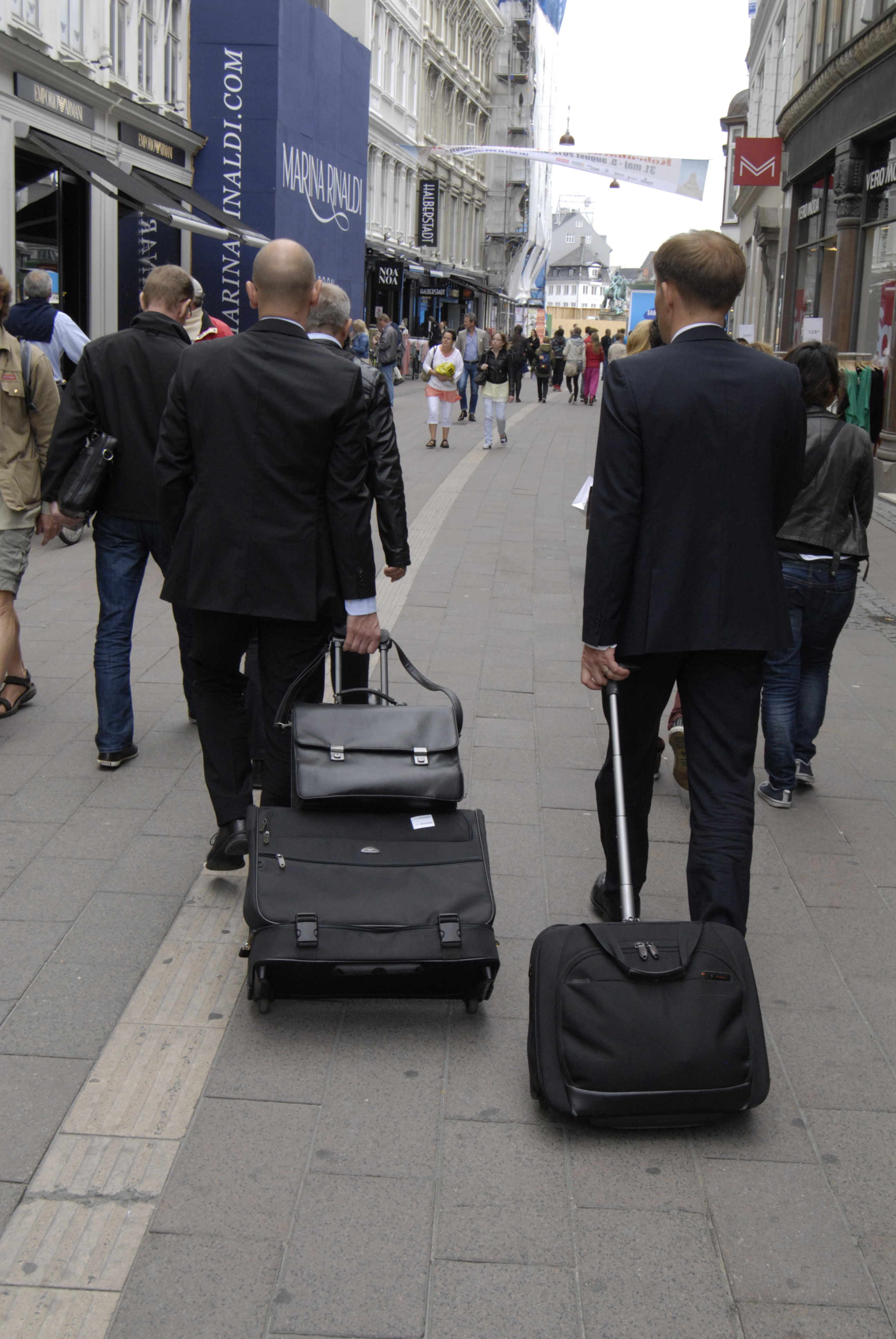 Businessmen with roller suitcases navigate a street in Copenhagen.