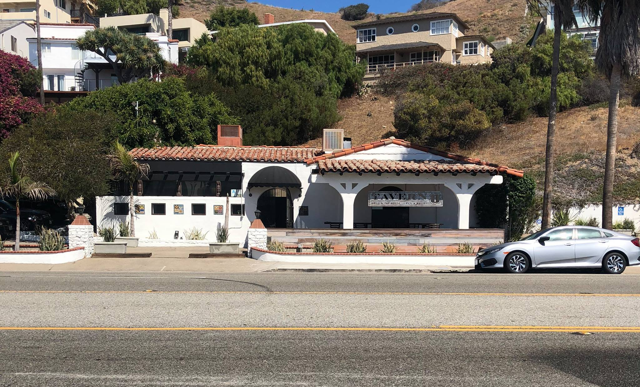 The Spanish-style restaurant, sitting along the road, is white with a green hillside in the background.
