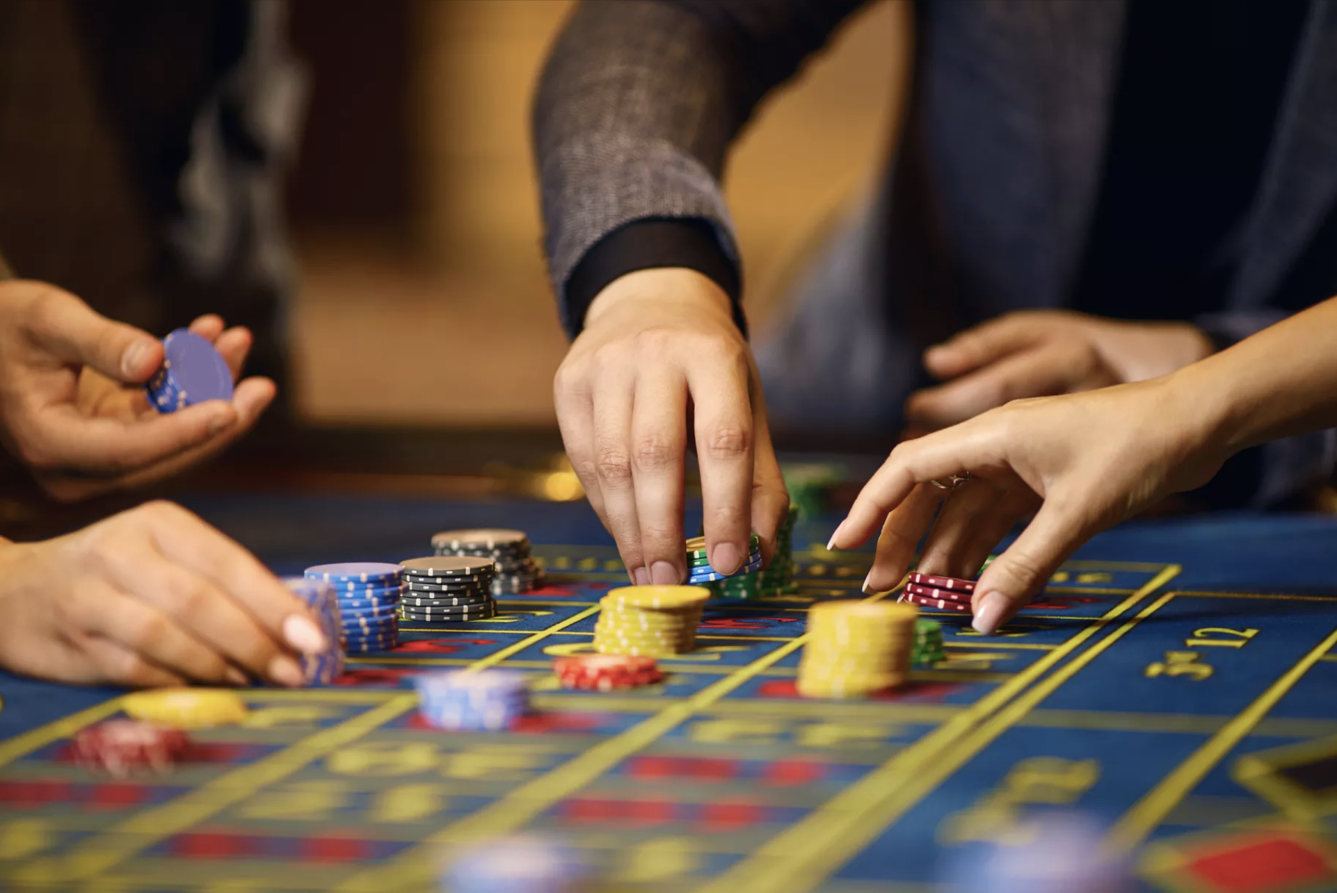 A close-up view of hands placing multicolor gambling chips on a blue gaming table.
