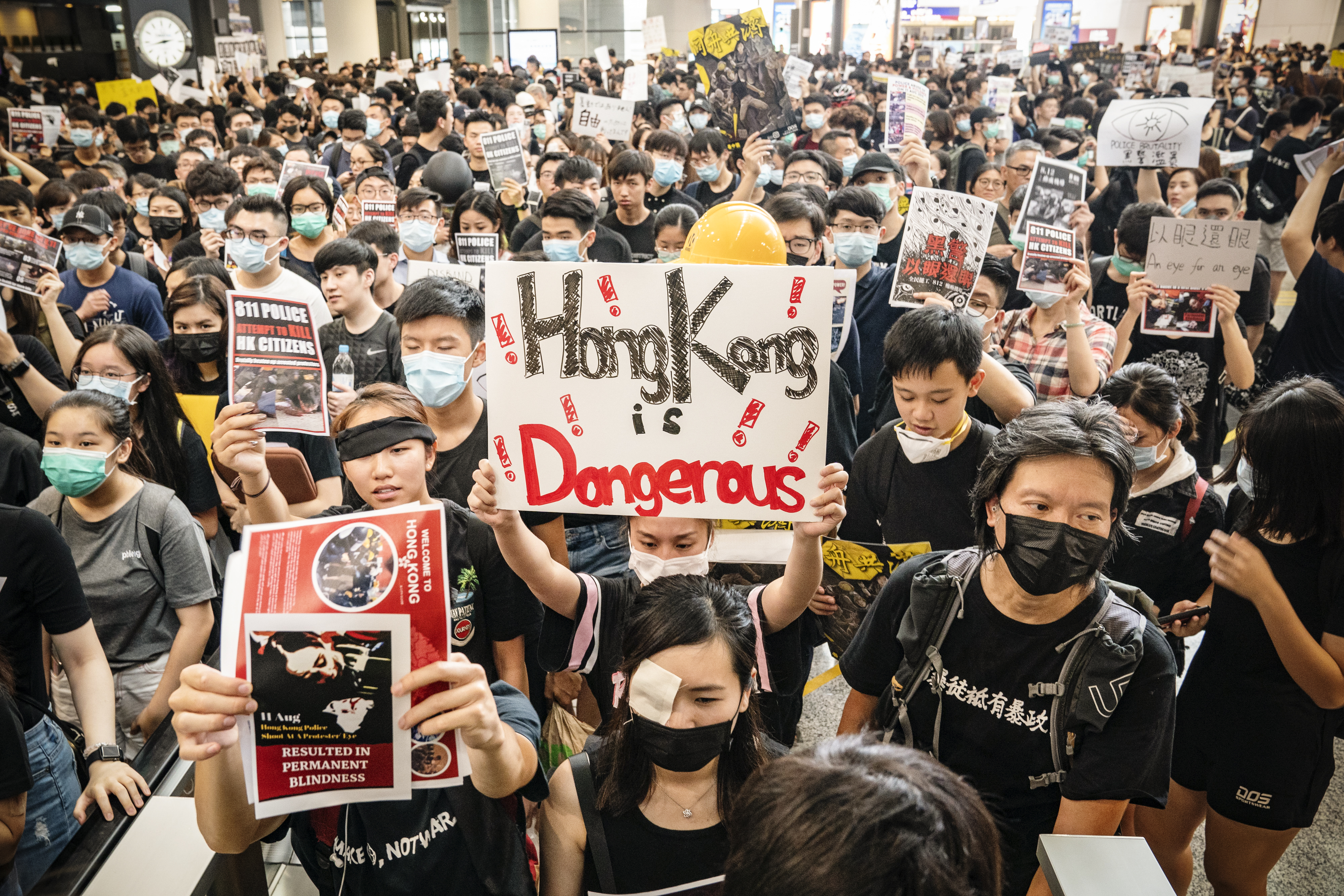 "Protesters, some wearing masks over their noses and mouths, carry signs, one of which reads ""Hong Kong is dangerous,"" and fill the arrivals hall in the Hong Kong international airport."