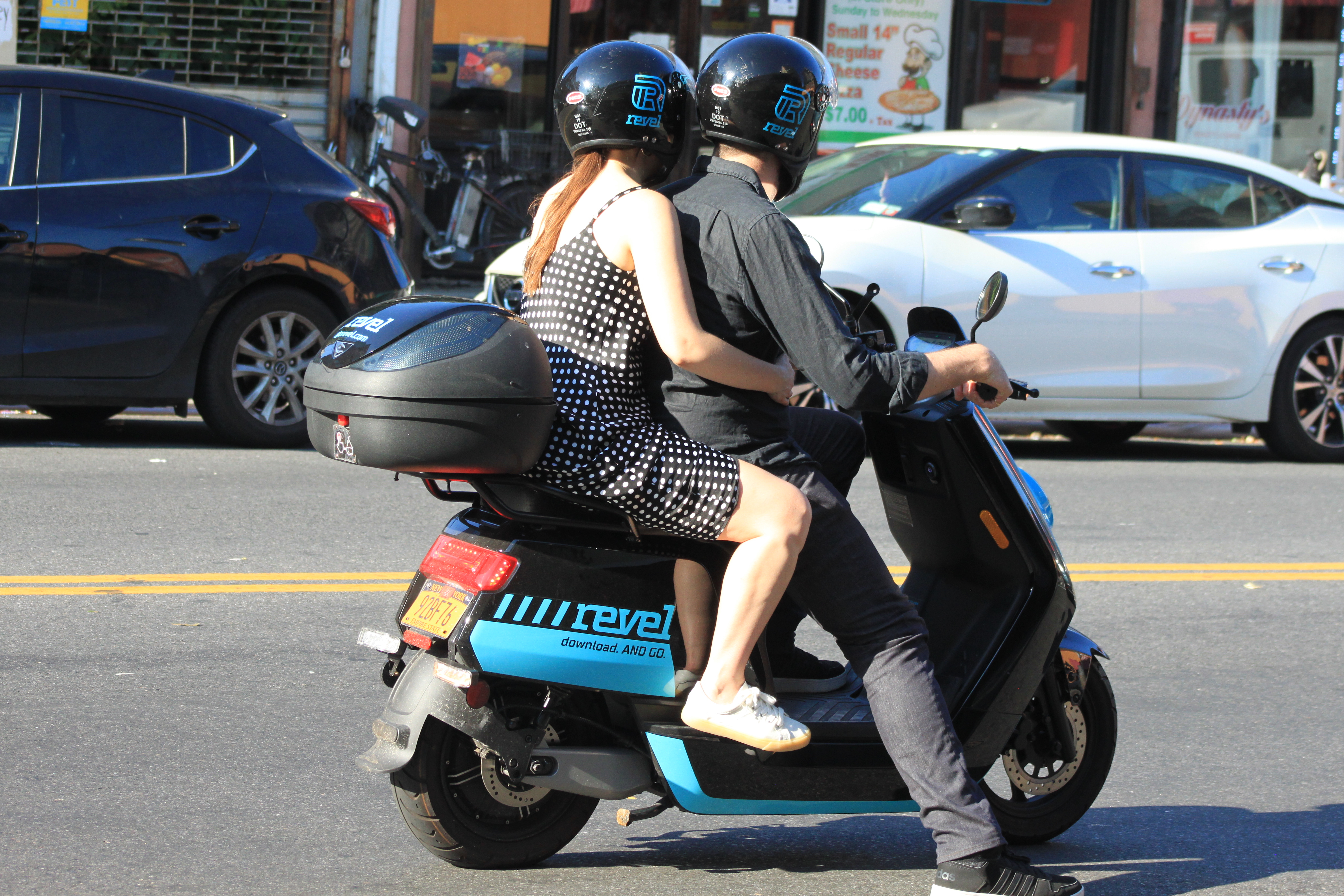 A man and a woman ride a blue Revel moped in New York. In the background, cars are parked on the street.