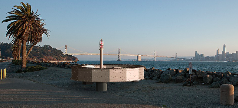 A rendering of a 25-foot steel ring on Treasure Island, with the Bay Bridge and SF skyline in the background.