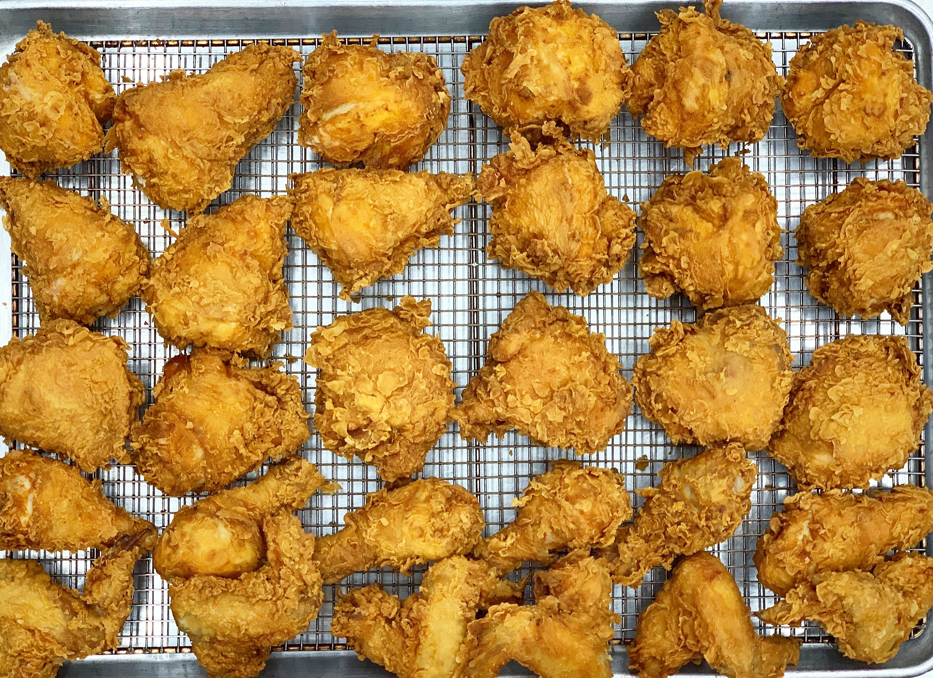 A wire tray of fried chicken pieces from above