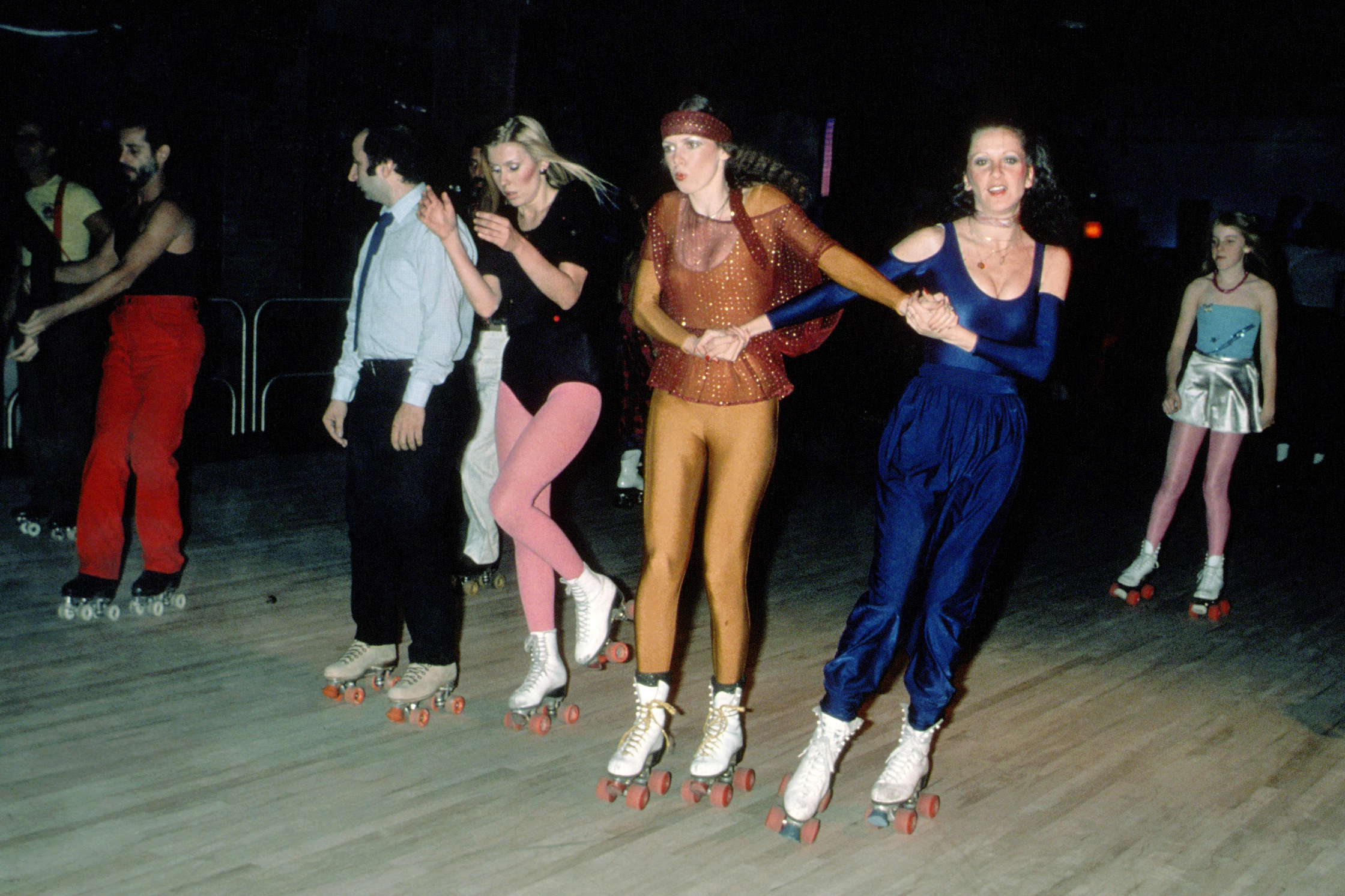 People roller skating in flamboyant 1970s apparel
