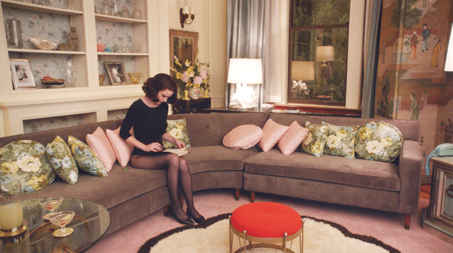 A scene from the Marvelous Mrs. Maisel includes a gray midcentury couch, red and gold ottoman, and floral and pink throw pillows.