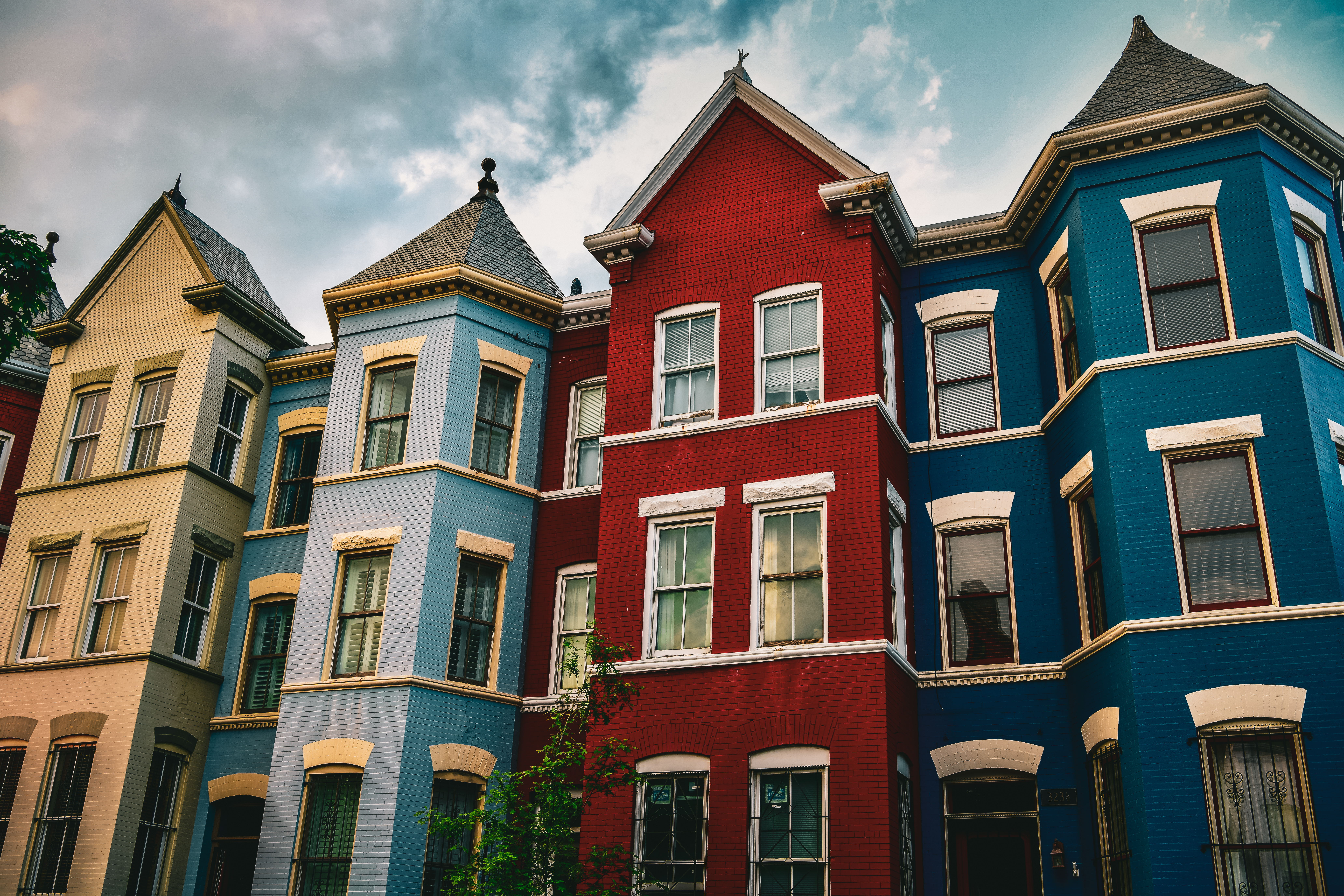 Four rowhouses in Washington, D.C. The first is beige, the second is light blue, the third is red, and the fourth is dark blue.