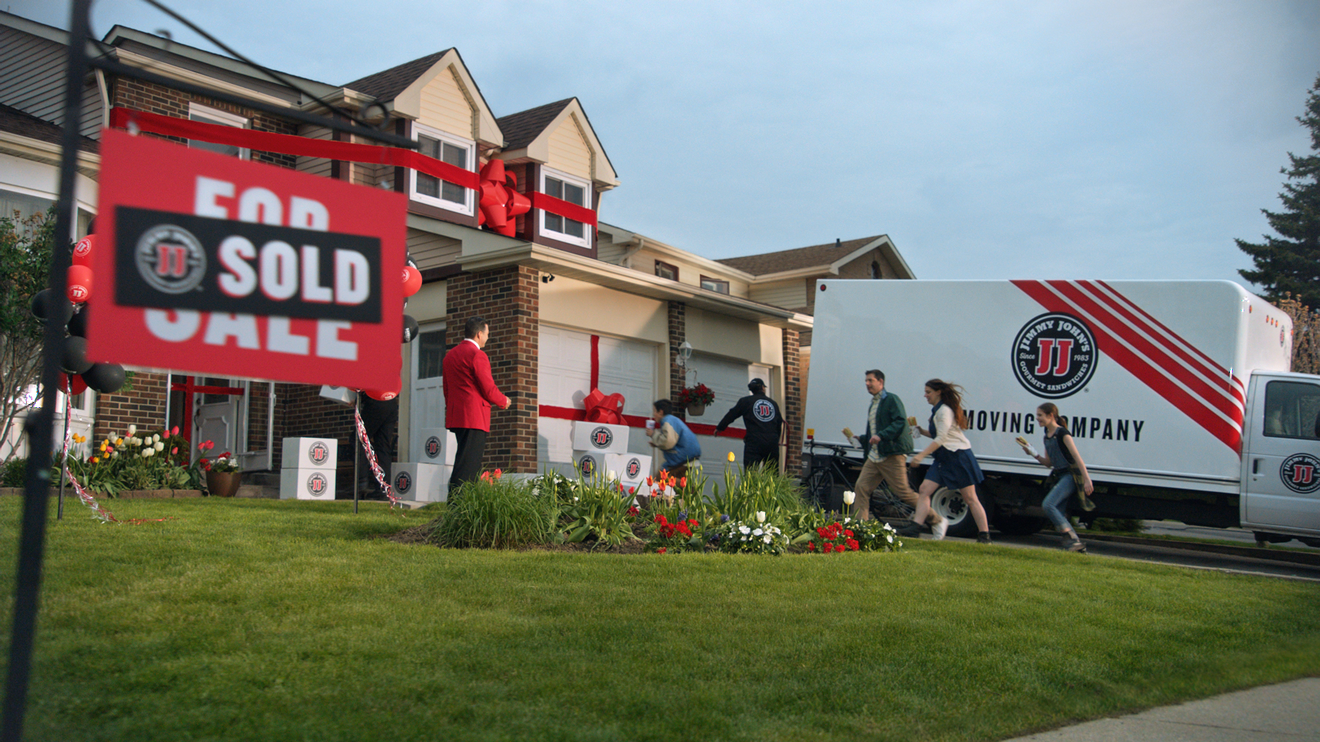 """A house with a """"sold"""" sign in front of it, and a moving truck in the driveway."""